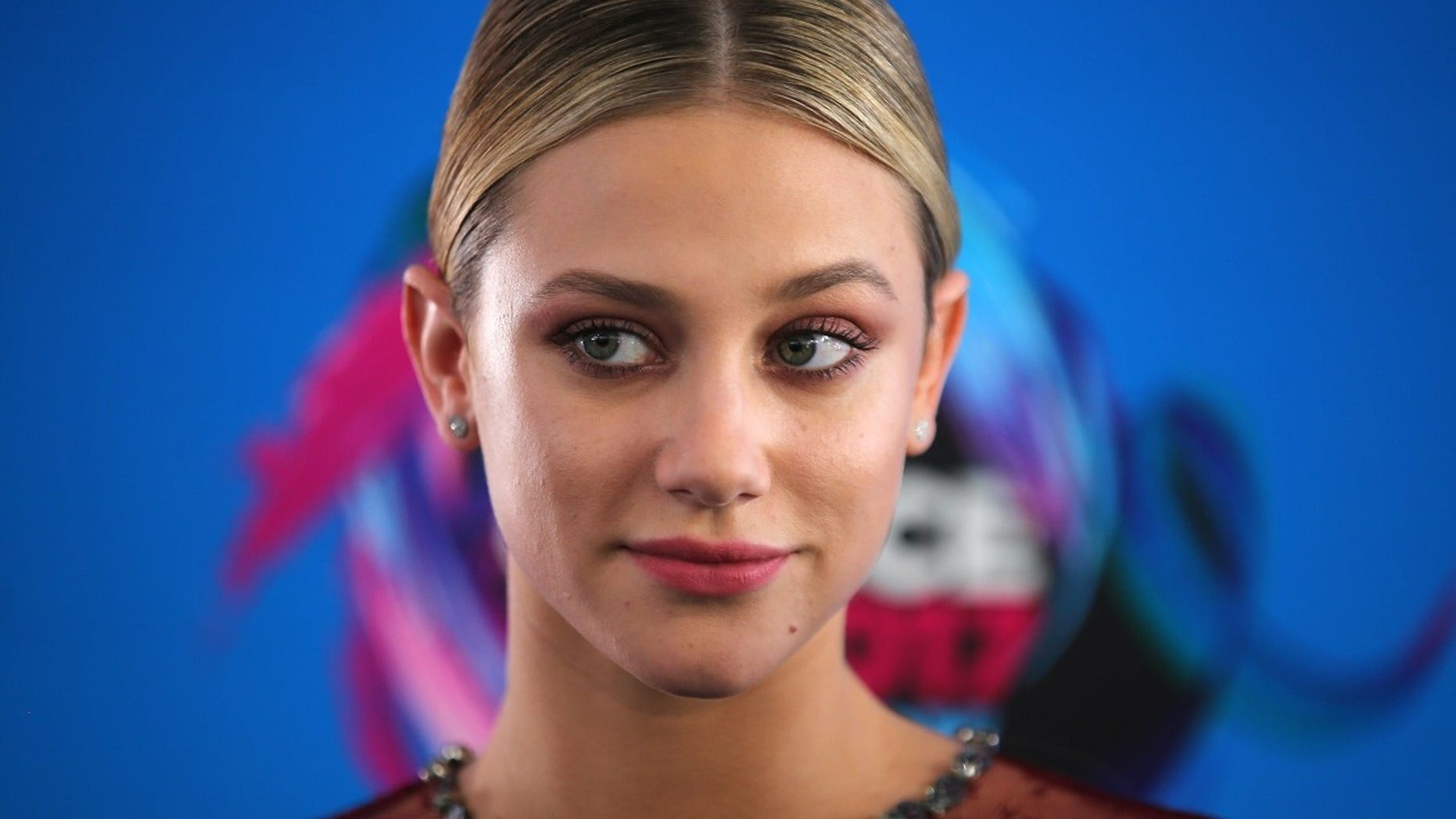 """lili Reinhart apologized on Sunday after she was accused of blackface when she tweeted out a photo of a """"demon"""" with her face painted black."""
