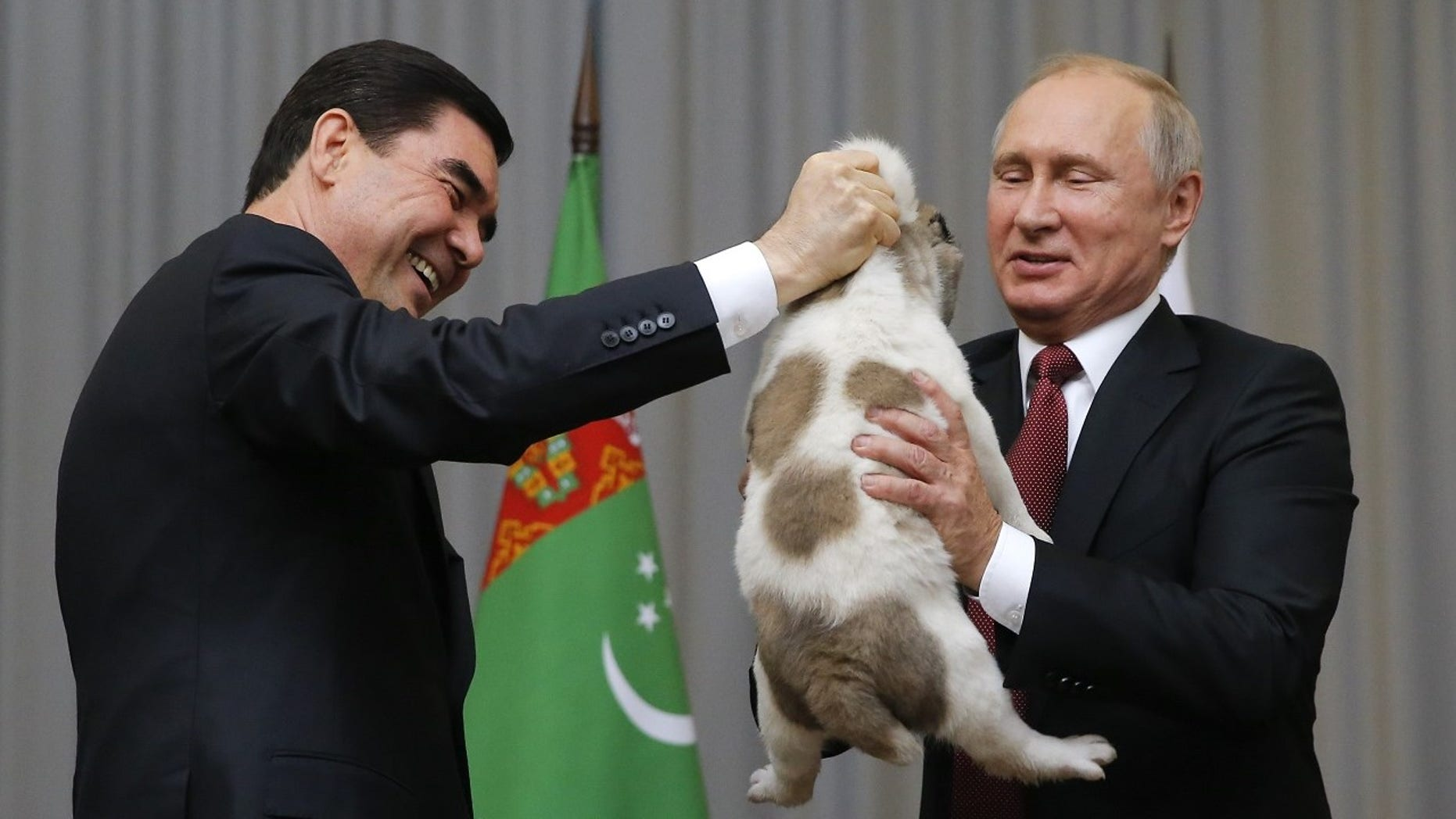 Turkmenistan's President Gurbanguly Berdimuhamedov, left, presents a Turkmen shepherd dog to Russian President Vladimir Putin.