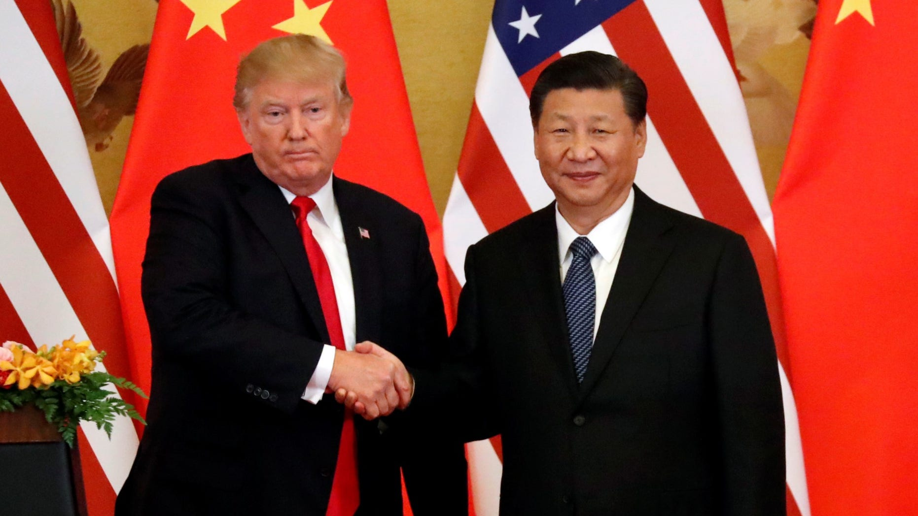 FILE -- President Donald Trump and China's President Xi Jinping make joint statements at the Great Hall of the People in Beijing, China, November 9, 2017.