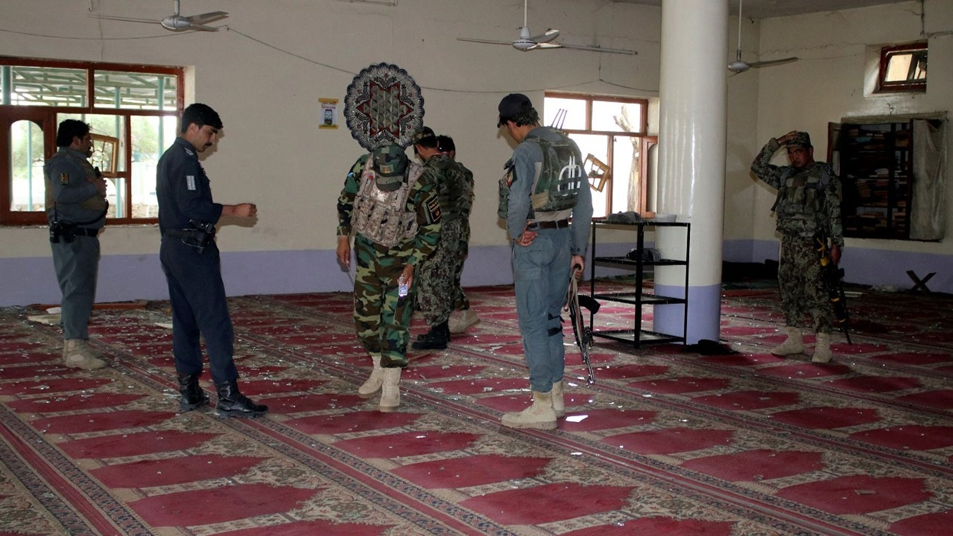 Afghan policemen inspect a mosque after a blast in Khost province.