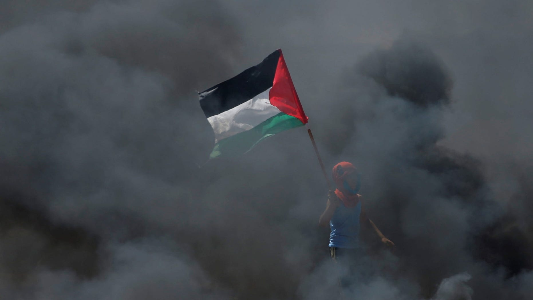 FILE -- A boy holds a Palestinian flag as he stands amidst smoke during a protest against U.S. embassy move to Jerusalem.