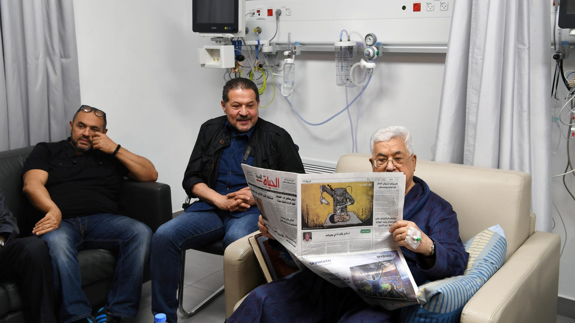 Palestinian President Mahmoud Abbas reads a newspaper inside the hospital in Ramallah, in the occupied West Bank May 21, 2018.