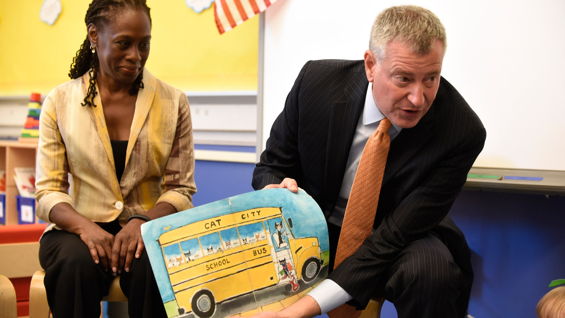 New York City Mayor Bill de Blasio (R) reads a book to pre-K students on their first day of school at Public School 59 in Staten Island, New York, September 9, 2015.  At left is First Lady Chirlane McCray.  REUTERS/Barry Williams/Pool