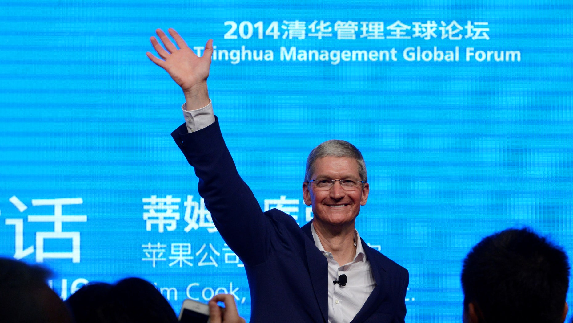 Apple CEO Tim Cook waves as he attends a talk in Beijing October 23, 2014.