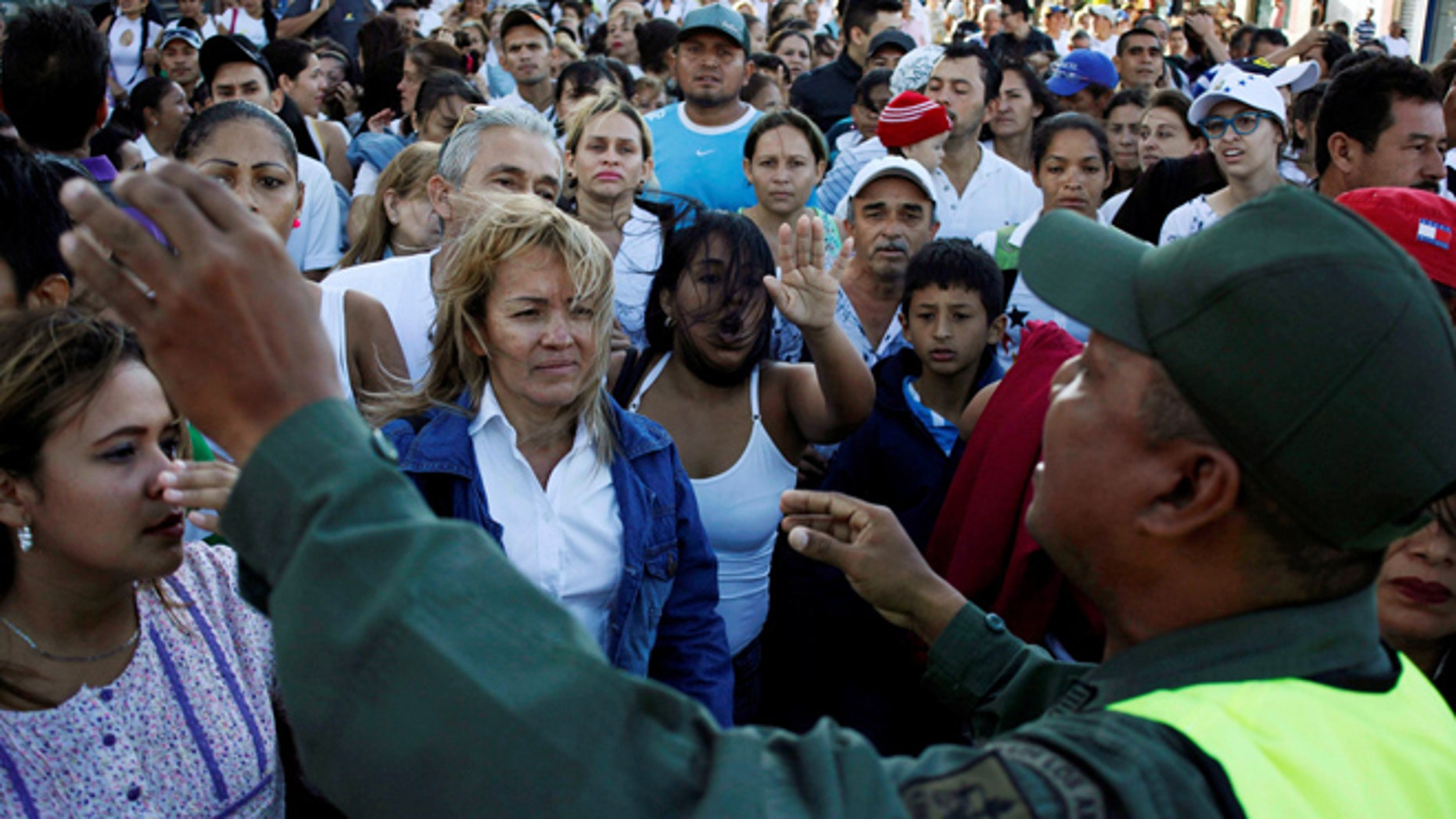 Venezuelan citizens listen to a national guardsman as they try to cross over the Simon Bolivar international bridge to Colombia to take advantage of the temporary border opening in San Antonio del Tachira. (REUTERS)