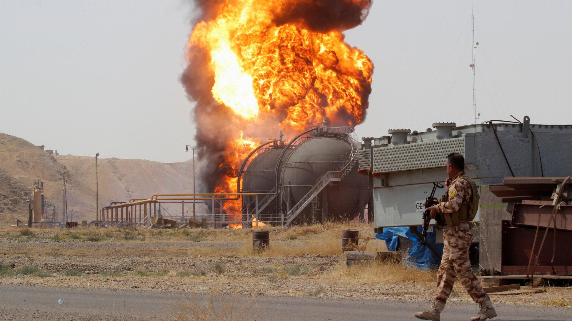 A member of the Kurdish Peshmerga forces walks as smoke rises after an attack at Bai Hassan oil station, northwest of Kirkuk, Iraq, July 31, 2016. REUTERS/Ako Rasheed - RTSKFNM