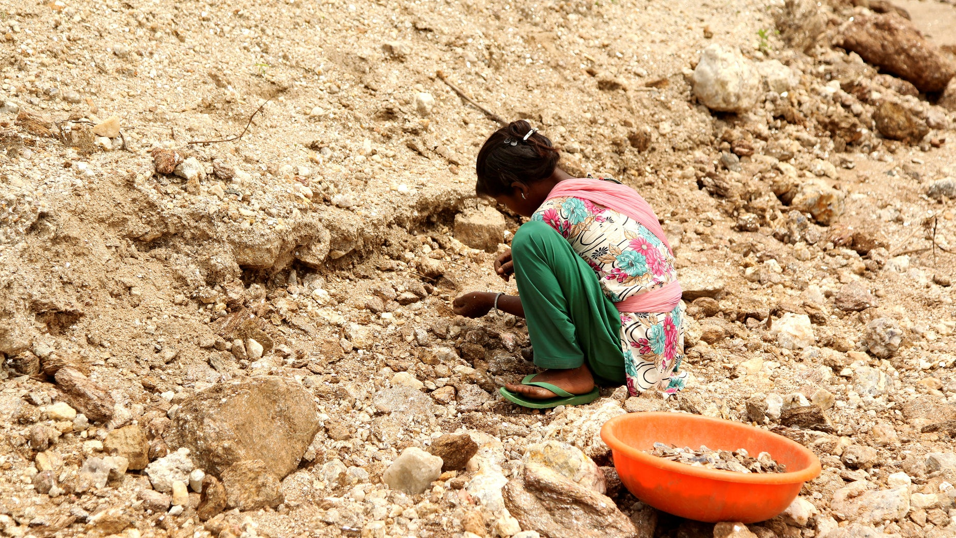 Gudiya, 13, breaks away pieces of mica from rocks in an illegal open cast mine in Koderma district in the eastern state of Jharkhand, India, June 29, 2016. Picture taken June 29, 2016. To match Thomson Reuters Foundation INDIA-MICA/CHILDREN REUTERS/Nita Bhalla - RTSKS2A
