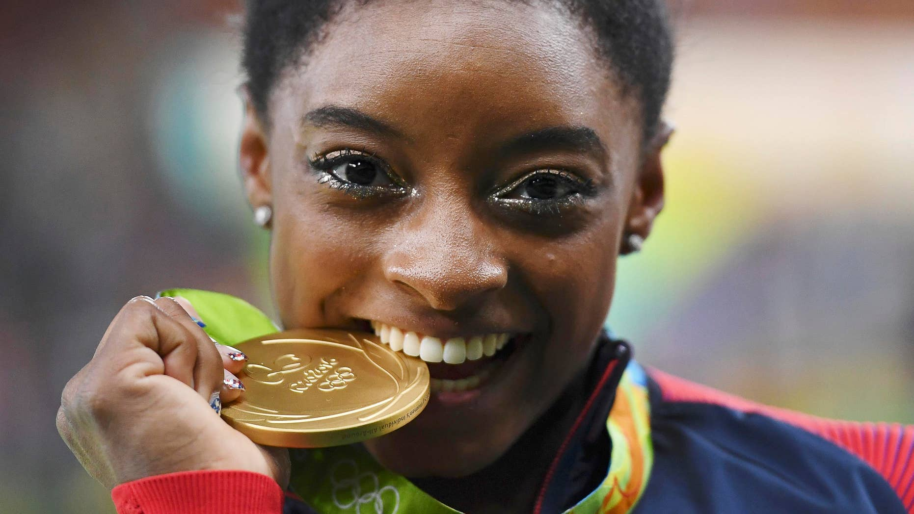 2016 Rio Olympics - Artistic Gymnastics - Victory Ceremony - Women's Individual All-Around Victory Ceremony - Rio Olympic Arena - Rio de Janeiro, Brazil - 11/08/2016. Simone Biles (USA) of USA bites her gold medal on the podium after winning the women's individual all-around final. REUTERS/Dylan Martinez TPX IMAGES OF THE DAY. FOR EDITORIAL USE ONLY. NOT FOR SALE FOR MARKETING OR ADVERTISING CAMPAIGNS. - RTSMS3U