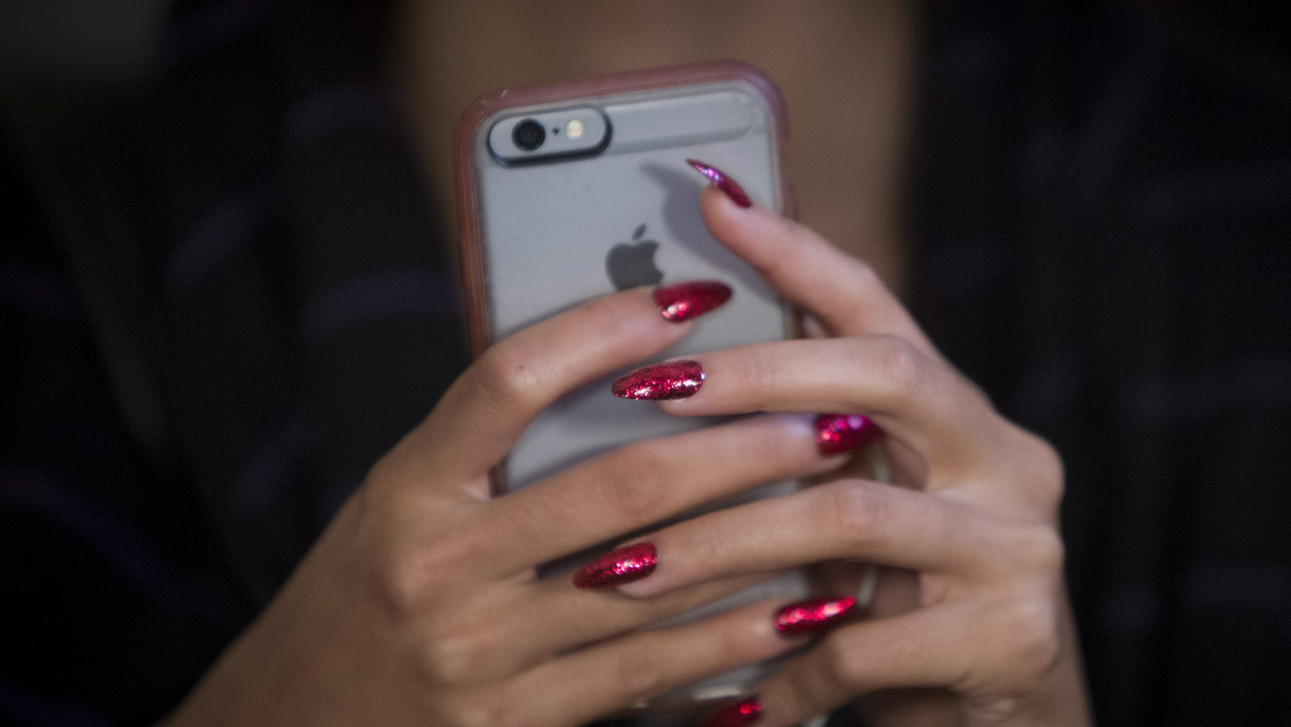 A model's nails are seen as she uses her cell phone backstage before the Betsey Johnson Spring/Summer 2016 collection presentation during New York Fashion Week in New York, September 11, 2015.