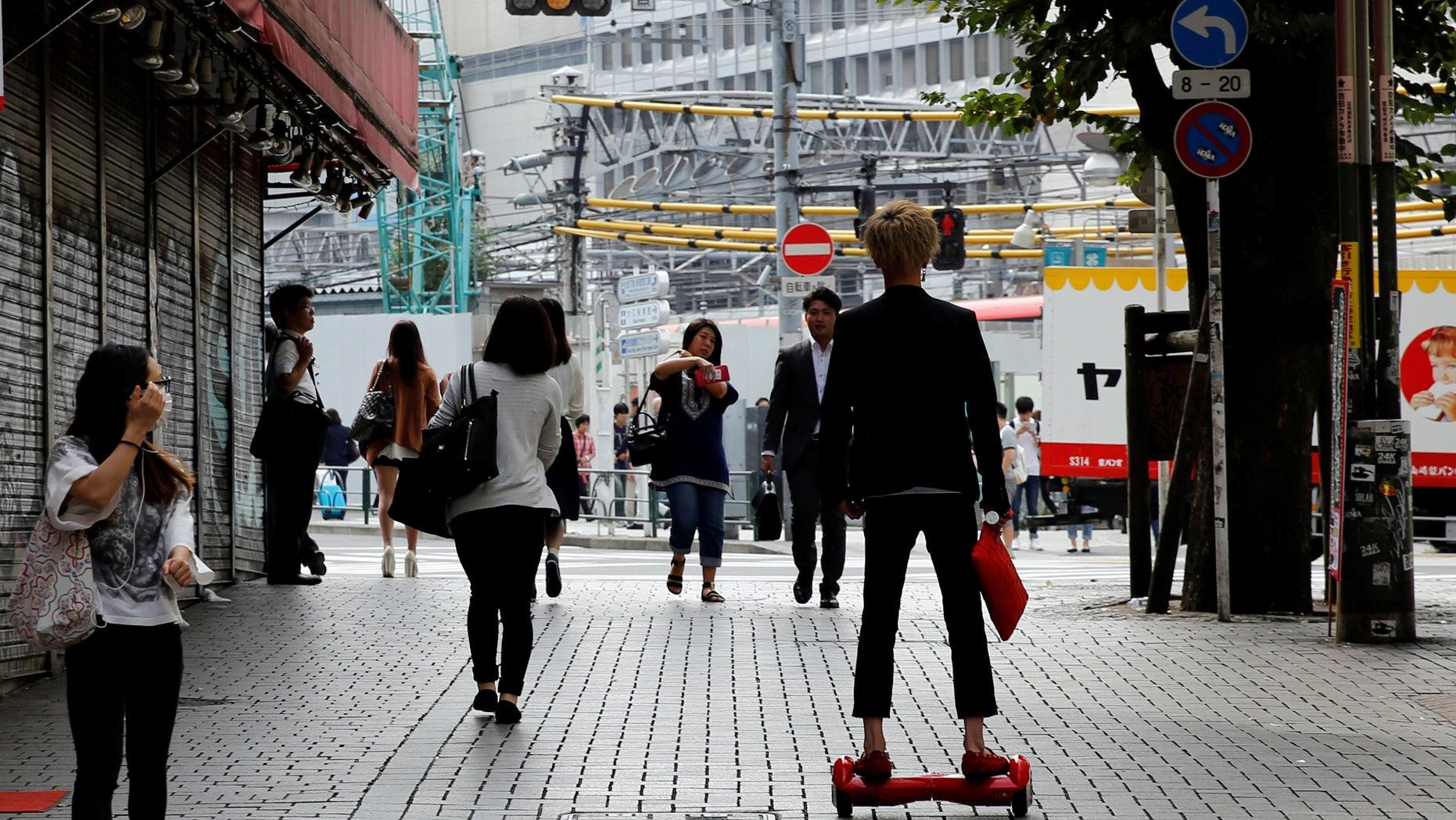 A man rides a hoverboard in Tokyo, Japan, September 29, 2016. (REUTERS/Toru Hanai)