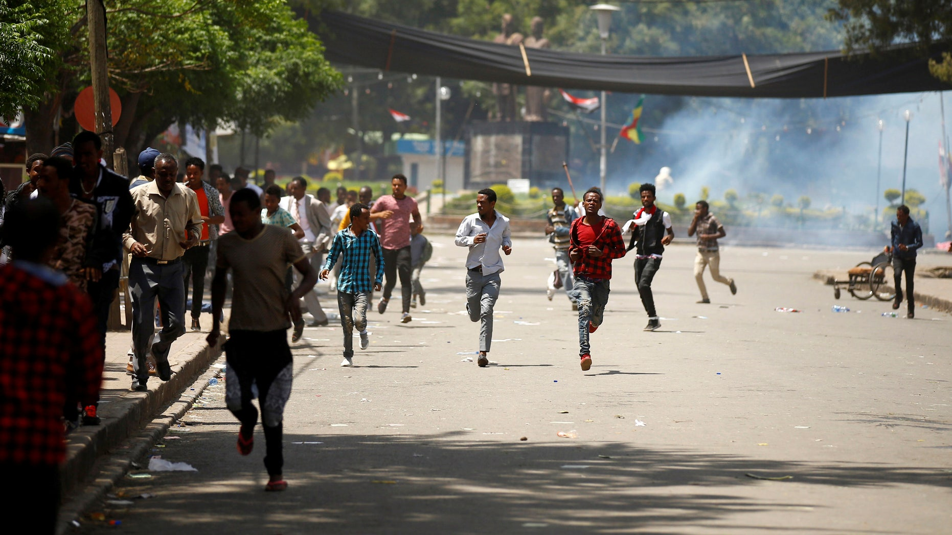 Protesters run from tear gas fired by police.