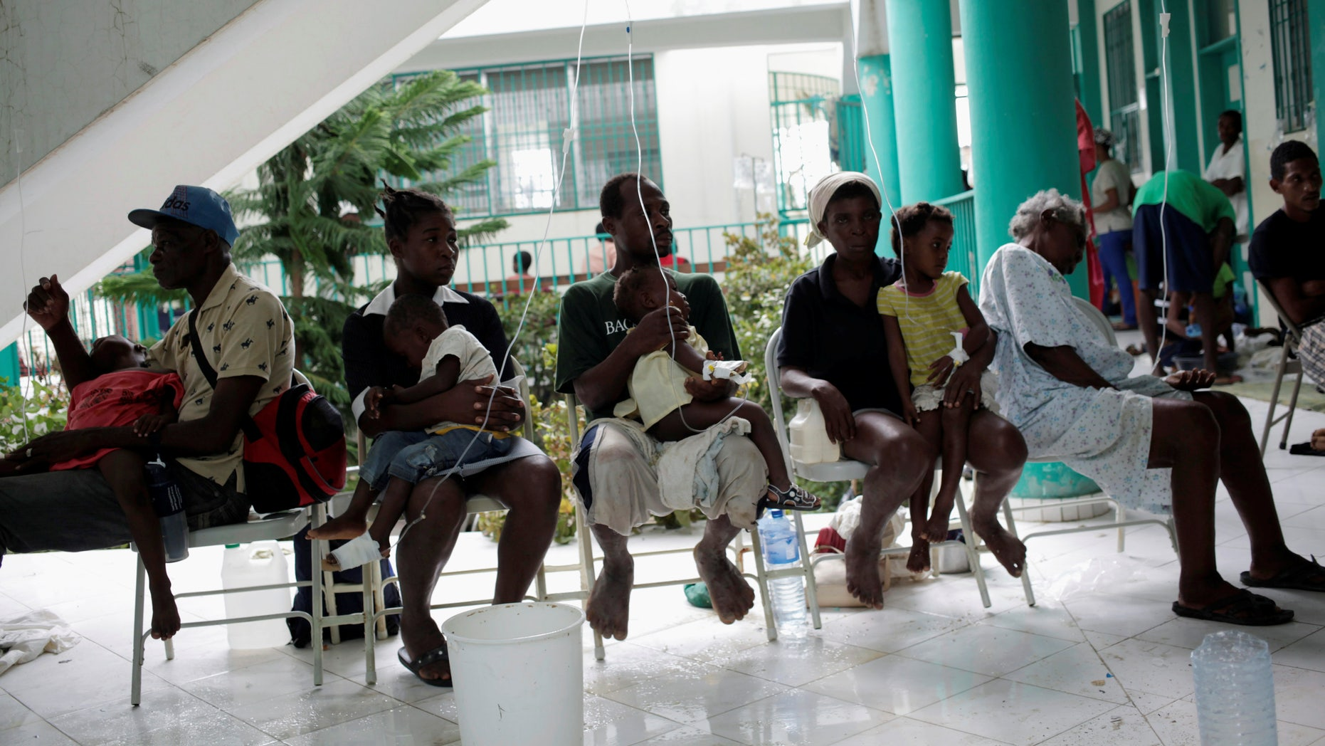 Adults hold children receiving treatment for cholera after Hurricane Matthew in the Hospital of Port-a-Piment, Haiti, October 9, 2016.
