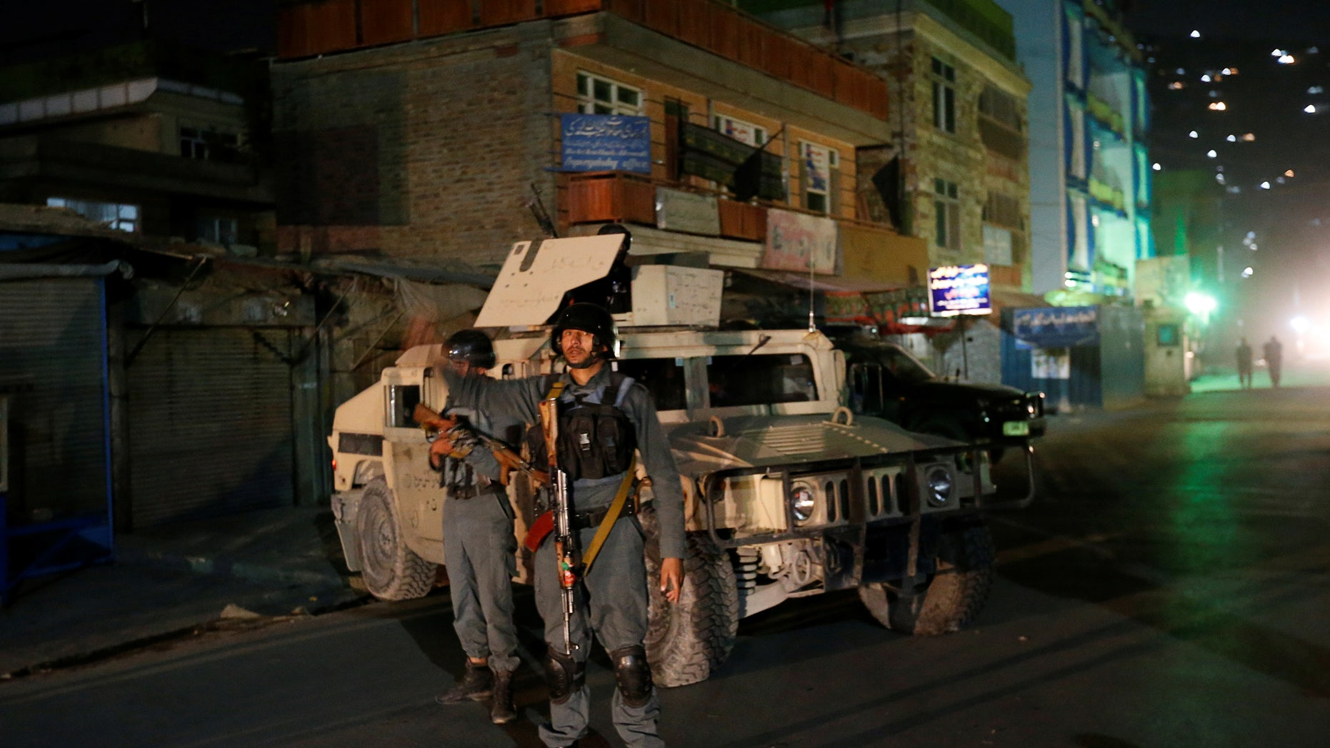 Afghan policemen stand guard near the site of the attack in Kabul.