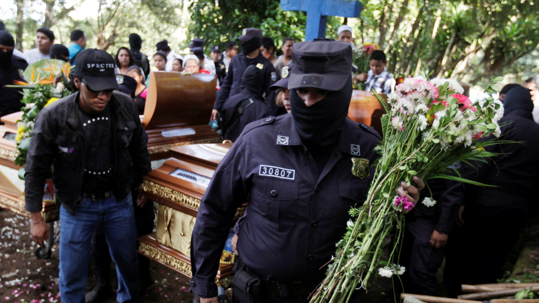 Salvadoran police officers participate in the funeral ceremony for their colleague Lorenzo Rojas Herrera and his son Marvin, who were killed by suspected gang members.