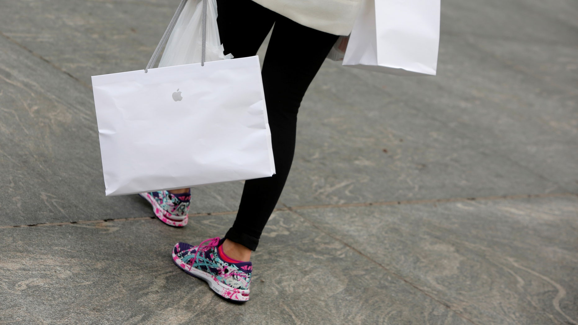 A woman carries purchases from the Apple Fifth Avenue store during Black Friday sales in Manhattan, New York, U.S., November 25, 2016. (REUTERS/Andrew Kelly)