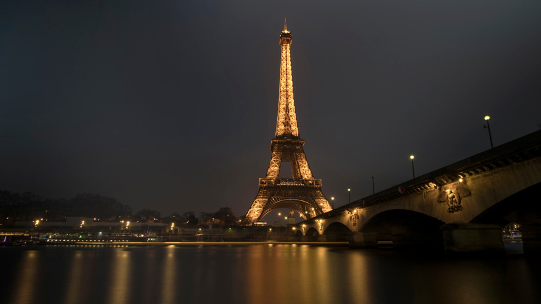 A streak of light from a passing boat is seen in this long time-exposure of the illuminated Eiffel Tower and the Seine River in Paris, France, January 17, 2017. REUTERS/Philippe Wojazer - RTSVY77
