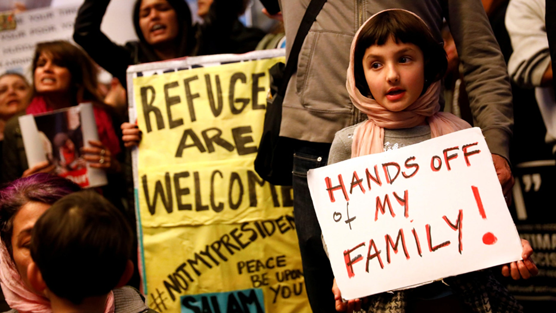Rosalie Gurna, 9, holds a sign in support of Muslim family members as people protest against U.S. President Donald Trump's travel ban on Muslim majority countries, at the International terminal at Los Angeles International Airport (LAX) in Los Angeles, California, U.S., January 28, 2017.