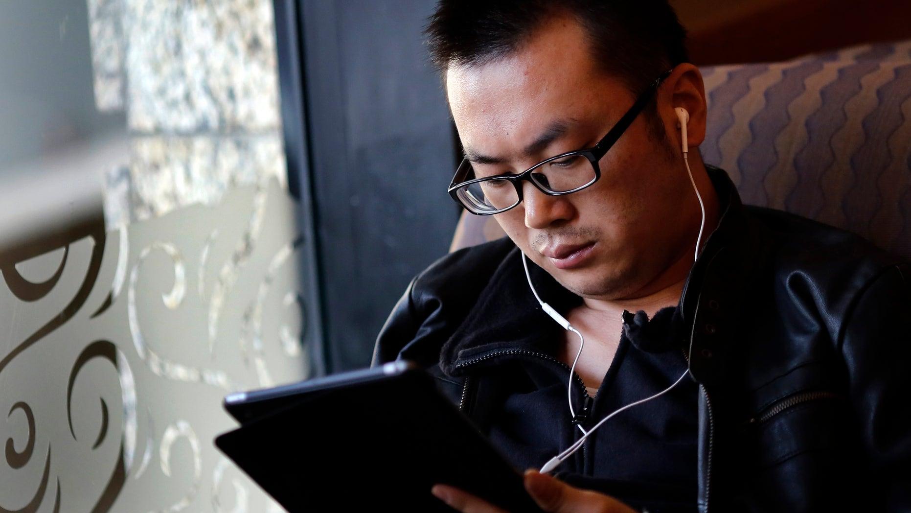 File photo. A man use his iPad inside a local coffee shop in downtown Shanghai November 28, 2013. (REUTERS/Carlos Barria)