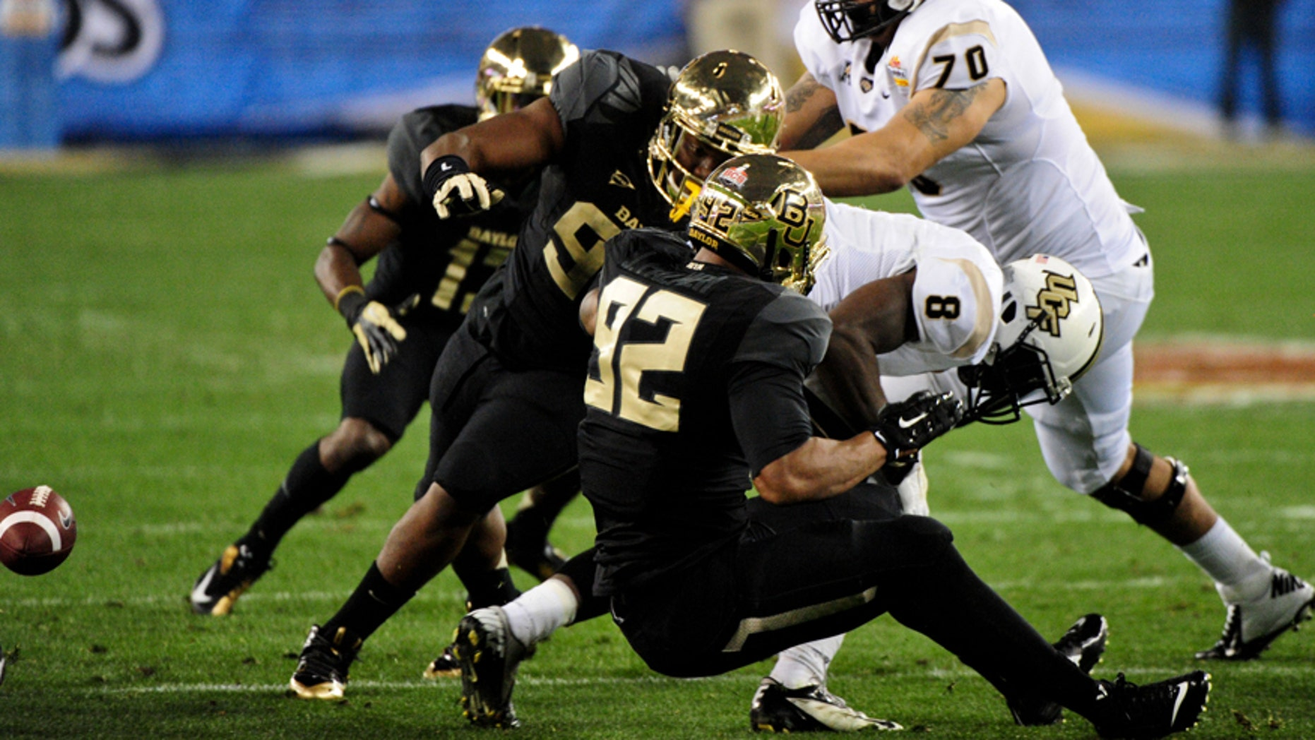 Jan 1, 2014; Glendale, AZ, USA; UCF Knights running back Storm Johnson (8) fumbles the ball while being tackled by Baylor Bears defensive lineman Byron Bonds (96) and defensive end Shawn Oakman (2) during the first half in the Fiesta Bowl at University of Phoenix Stadium. Mandatory Credit: Matt Kartozian-USA TODAY Sports - RTX16ZOV