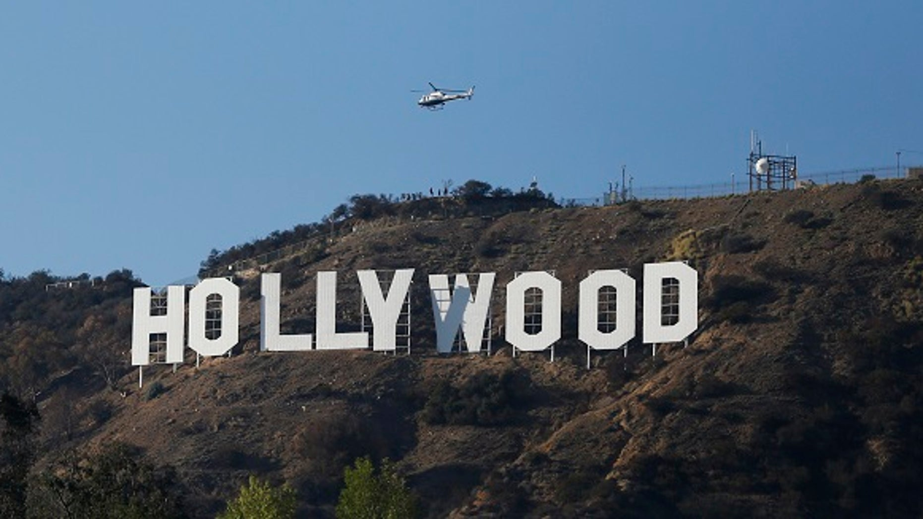 A Los Angeles Police Department (LAPD) helicopter flies over the Hollywood sign in Hollywood, California February 21, 2014. To match TRAVEL-HOLYWOOD  REUTERS/Mario Anzuoni  (UNITED STATES - Tags: ENTERTAINMENT ENVIRONMENT SOCIETY TRAVEL) - RTX19A0U