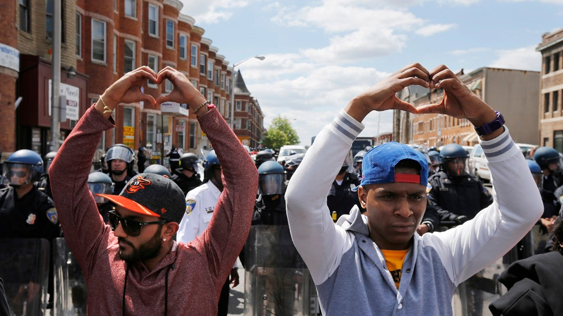 Members of the Baltimore community march in the street with police officers posted nearby.