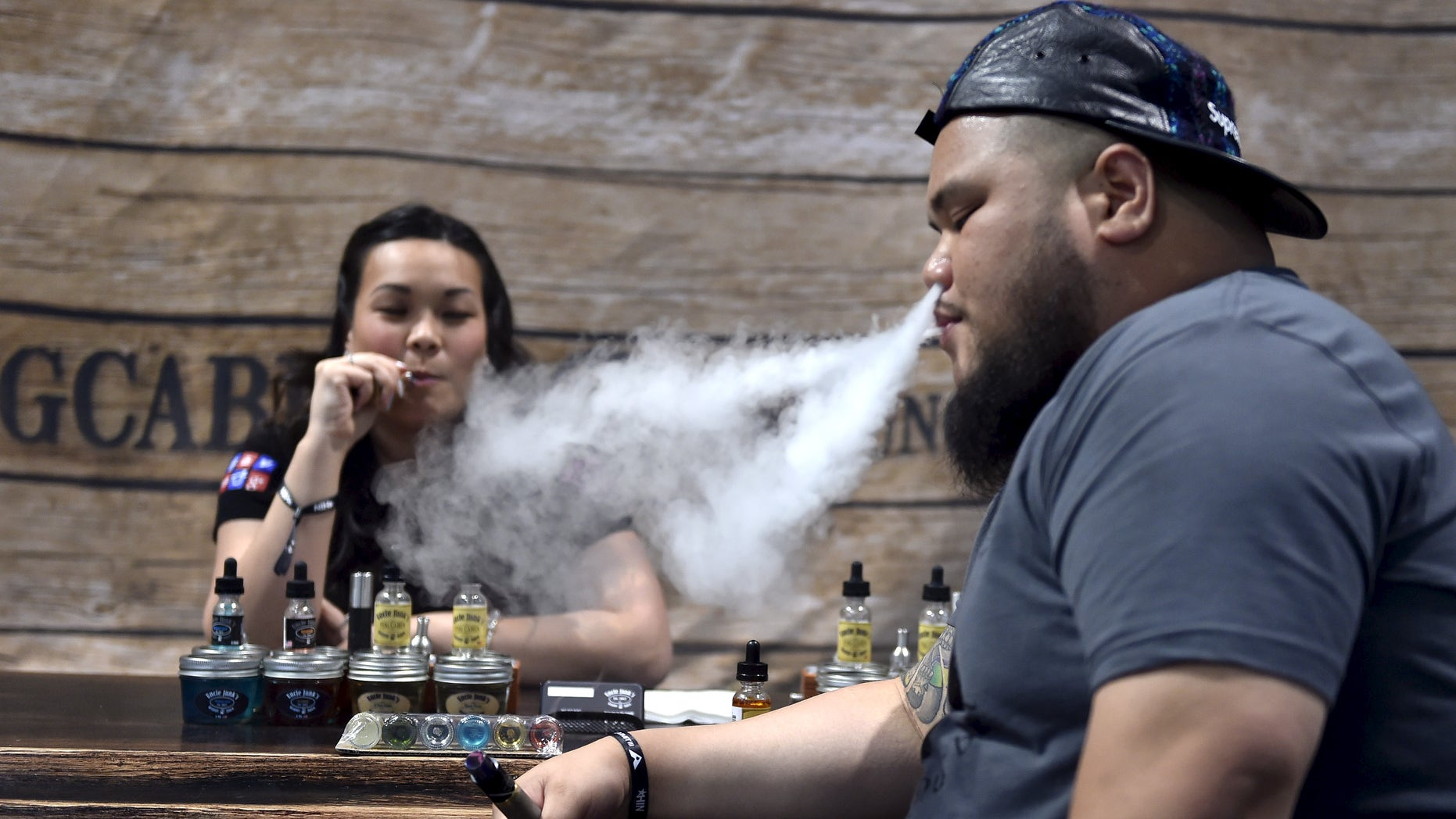 """Annie Young (L) and Dan Leano smoke e-cigarette at the Vape Summit 3 in Las Vegas, Nevada May 2, 2015. According to new research provided to Reuters, youngsters say that the flavors of the vaping liquids, and the """"ability to do tricks"""" are the top two reasons they consider electronic vaping devices cool. REUTERS/David Becker"""