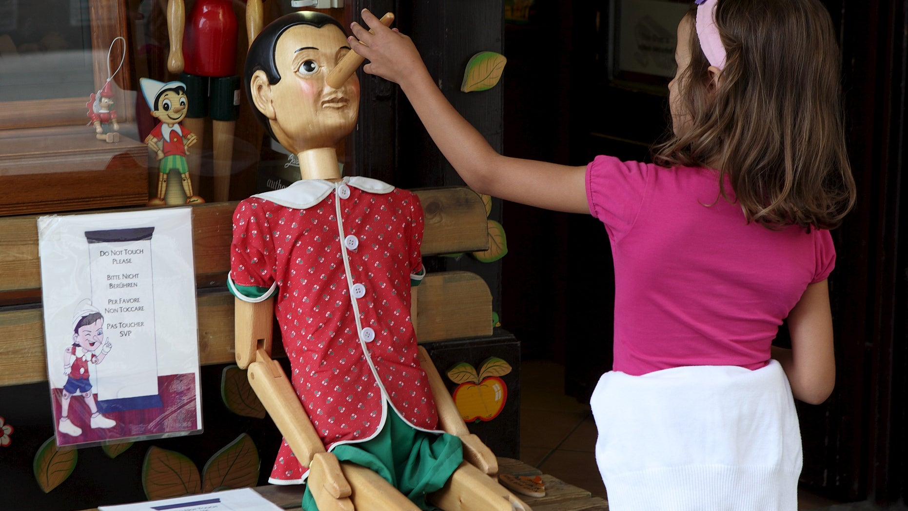 A child touches the nose of a Pinocchio puppet, a fictional character of a popular children's novel, at a woodwork souvenir shop in Vienna, Austria, August 21, 2015. (REUTERS/Heinz-Peter Bader)