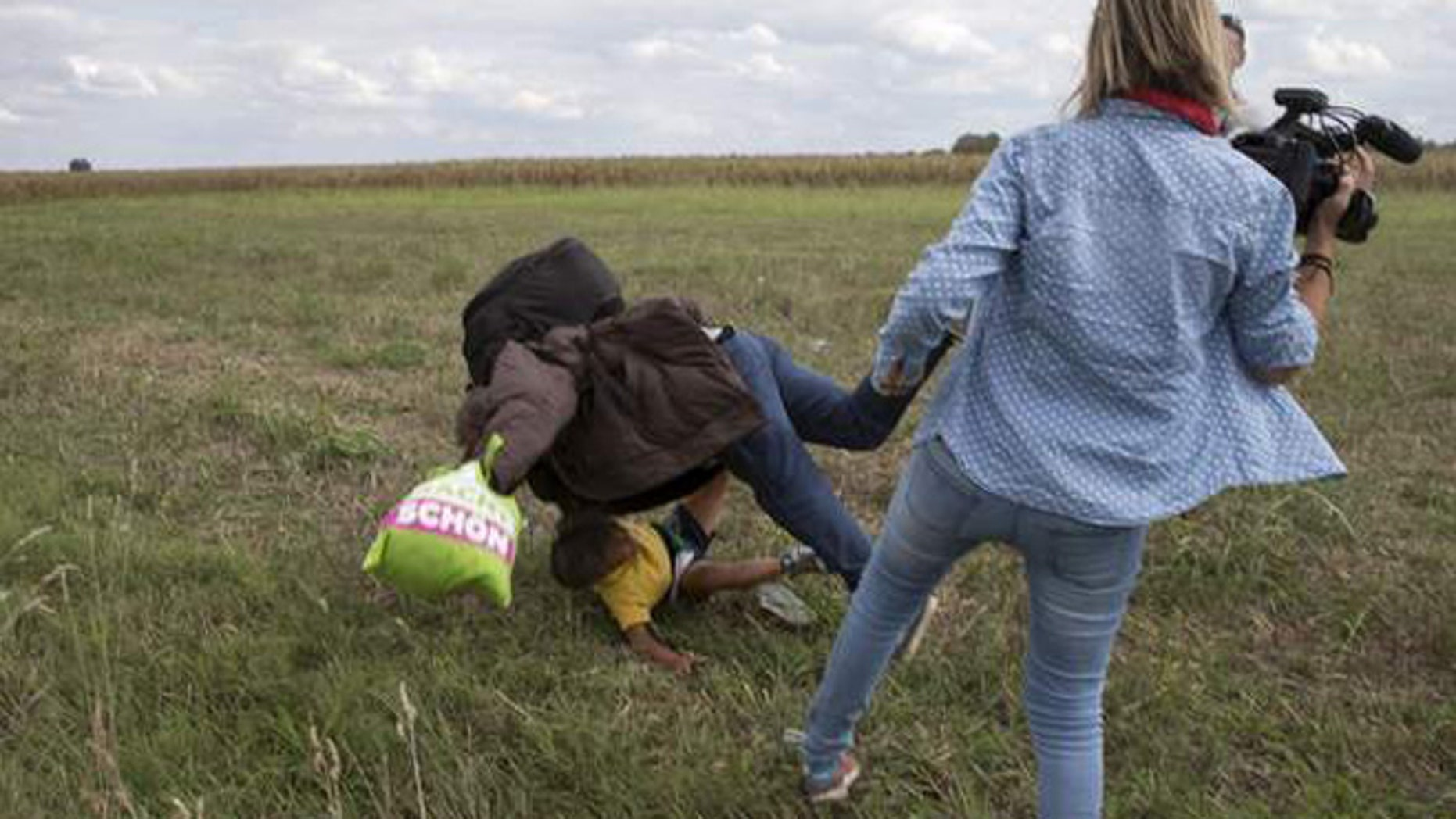 A camerawoman who was filmed tripping up a refugee says she plans to sue him.