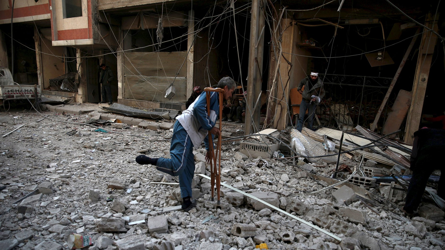 Dec. 13, 2015: Men search for belongings at a site hit by missiles in the Douma neighborhood of Damascus, Syria (REUTERS).