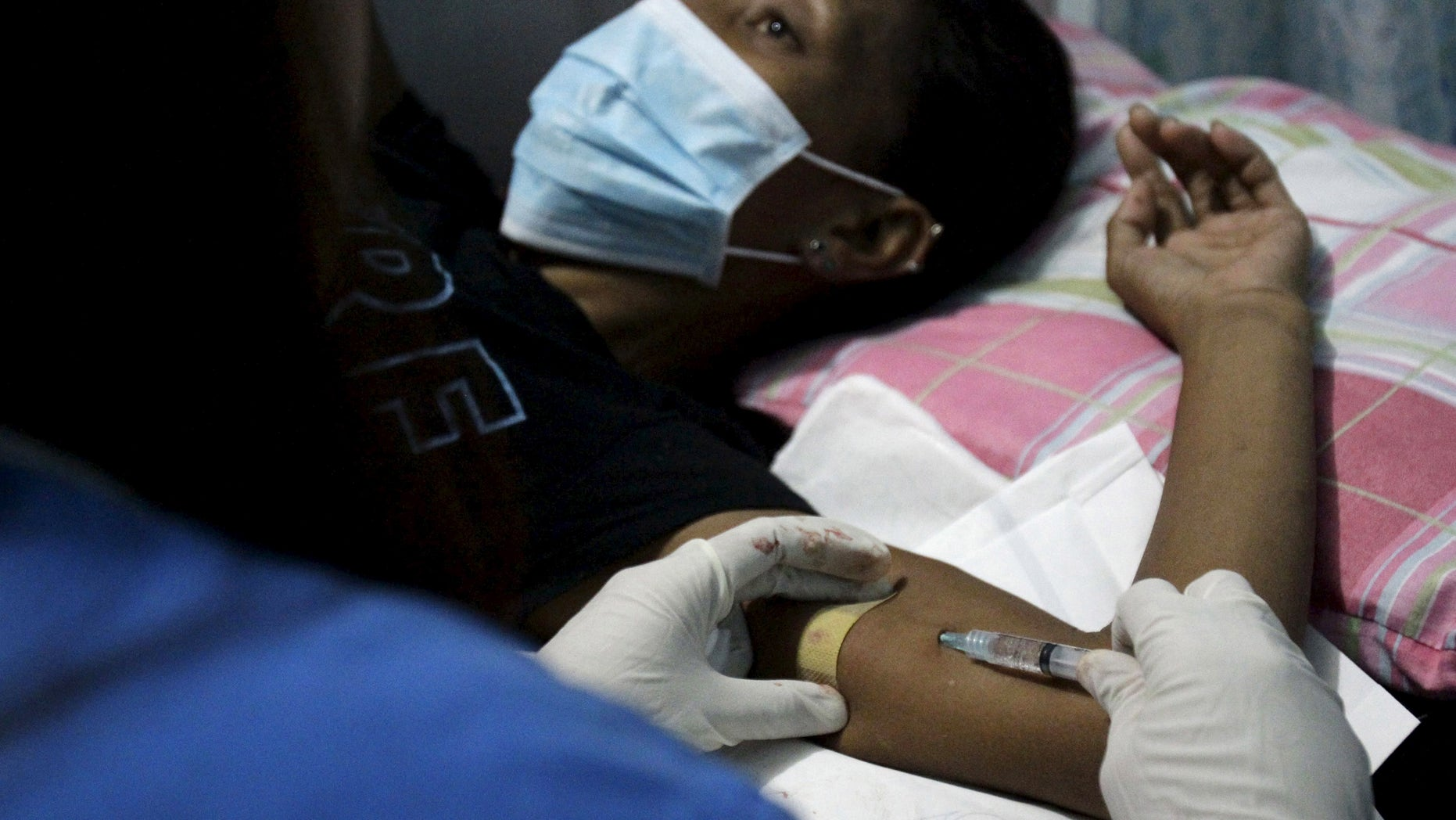 A health worker inserts an injectable contraceptive into a woman's arm during a reproductive health clinic run by an Non-Governmental Organization (NGO) in Tondo city, metro Manila January 12, 2016.