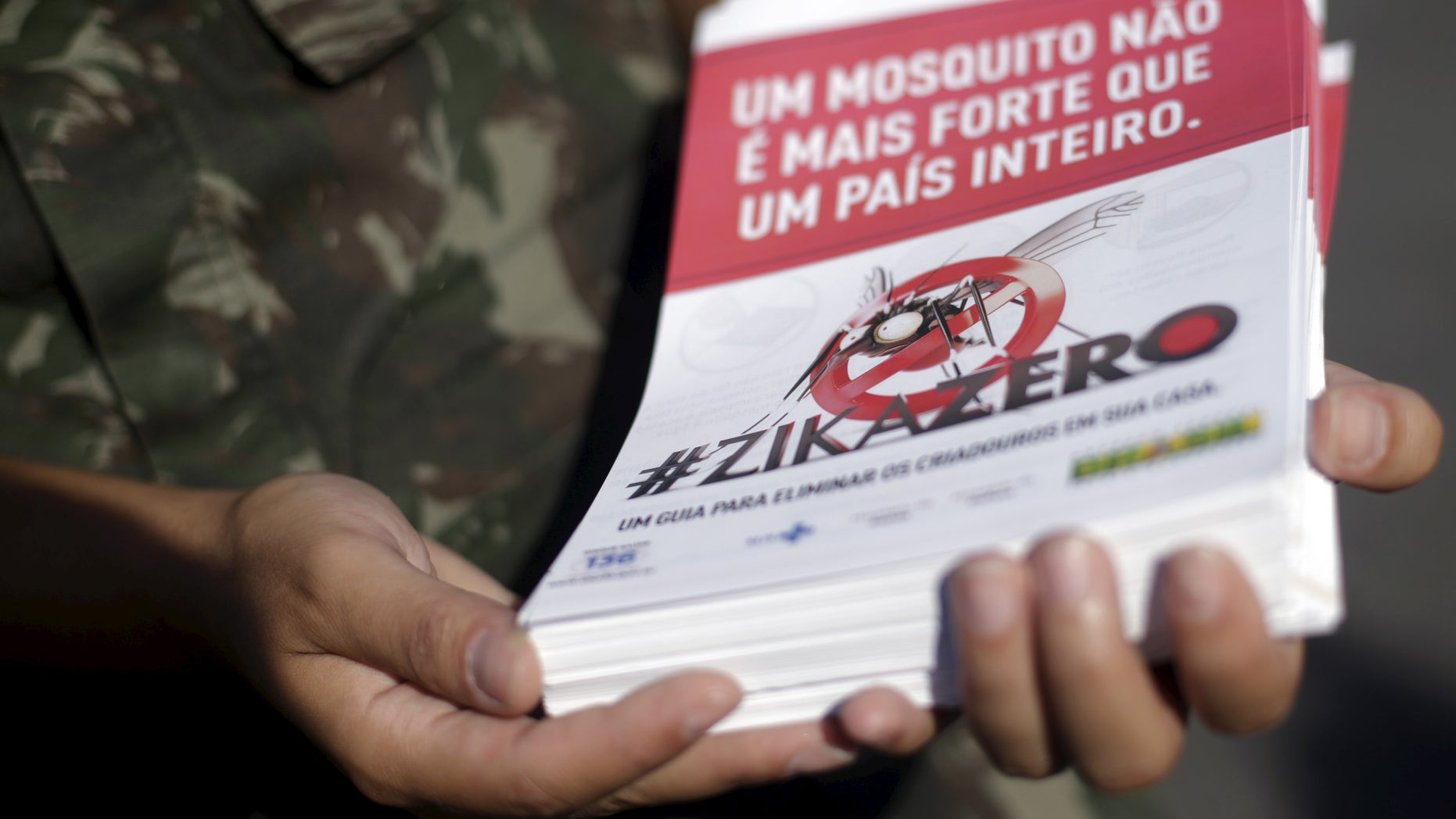 "A Brazilian Army soldier shows a pamphlet which will be distributed in the city, after a ceremony to mark the graduation from training on how to combat the Aedes aegypti mosquito in Rio de Janeiro, Brazil, February 12, 2016. The pamphlet reads, ""A mosquito is not stronger then an entire country."""