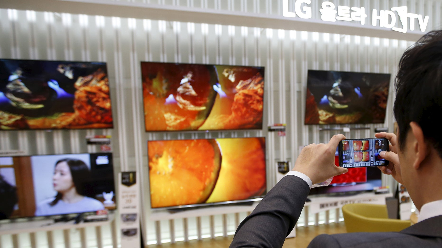 File photo: An employee takes photographs of LG Electronics' organic light-emitting diode (OLED) TV sets, which are made with LG Display flat screens, at its store in Seoul January 28, 2015. (REUTERS/Kim Hong-Ji)