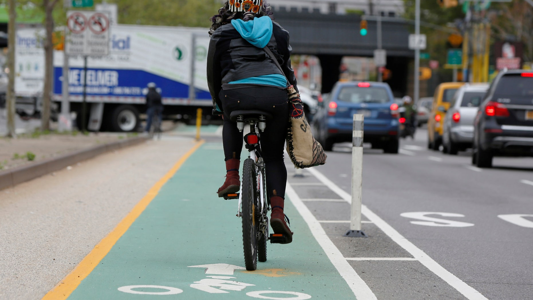 A woman rides a bicycle along a designated bike lane on Queens Boulevard in the borough of Queens in New York, U.S., May 5, 2016.