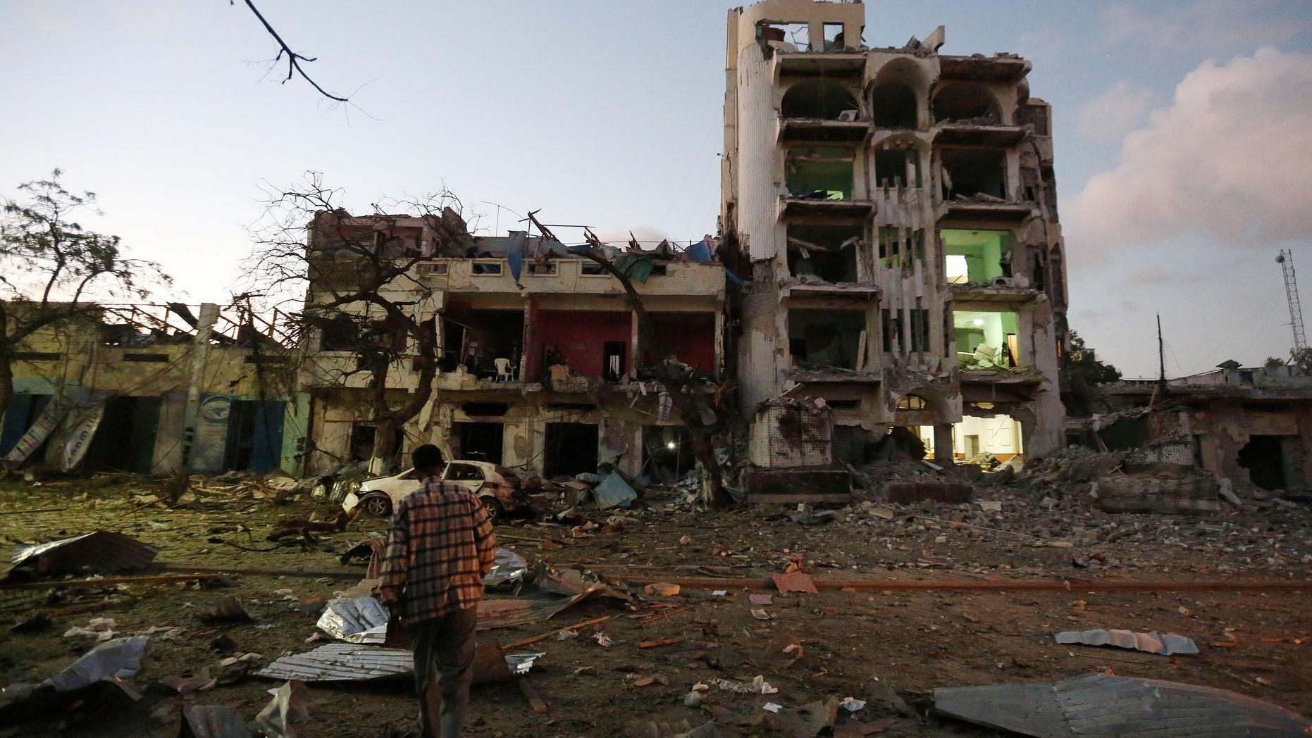 June 1, 2016: A man walks at the scene of a suicide car bombing outside Hotel Ambassador on Maka Al Mukaram Road in Somalia's capital Mogadishu. (Reuters)