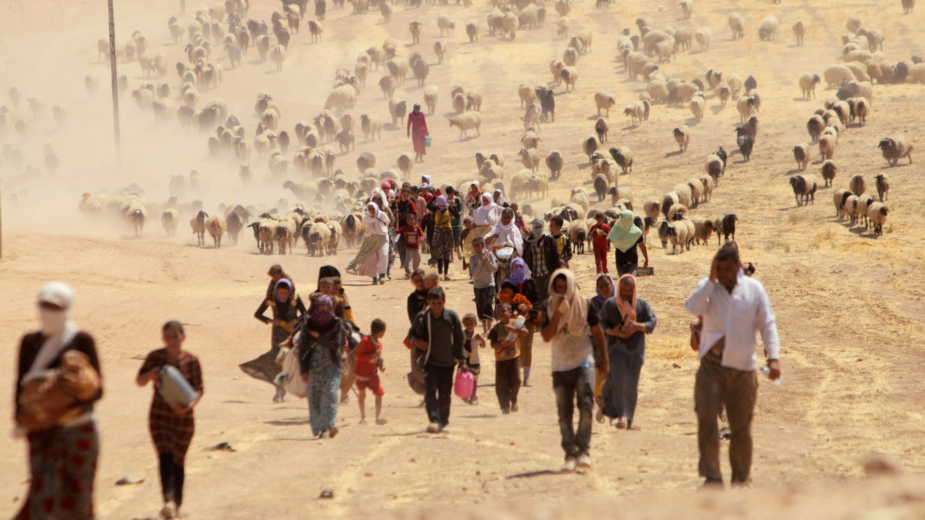 Displaced people from the minority Yazidi sect, fleeing violence from forces loyal to the Islamic State in Sinjar town, walk towards the Syrian border, on the outskirts of Sinjar mountain, near the Syrian border town of Elierbeh of Al-Hasakah Governorate August 10, 2014. REUTERS/Rodi Said/File Photo - RTX2GIYQ