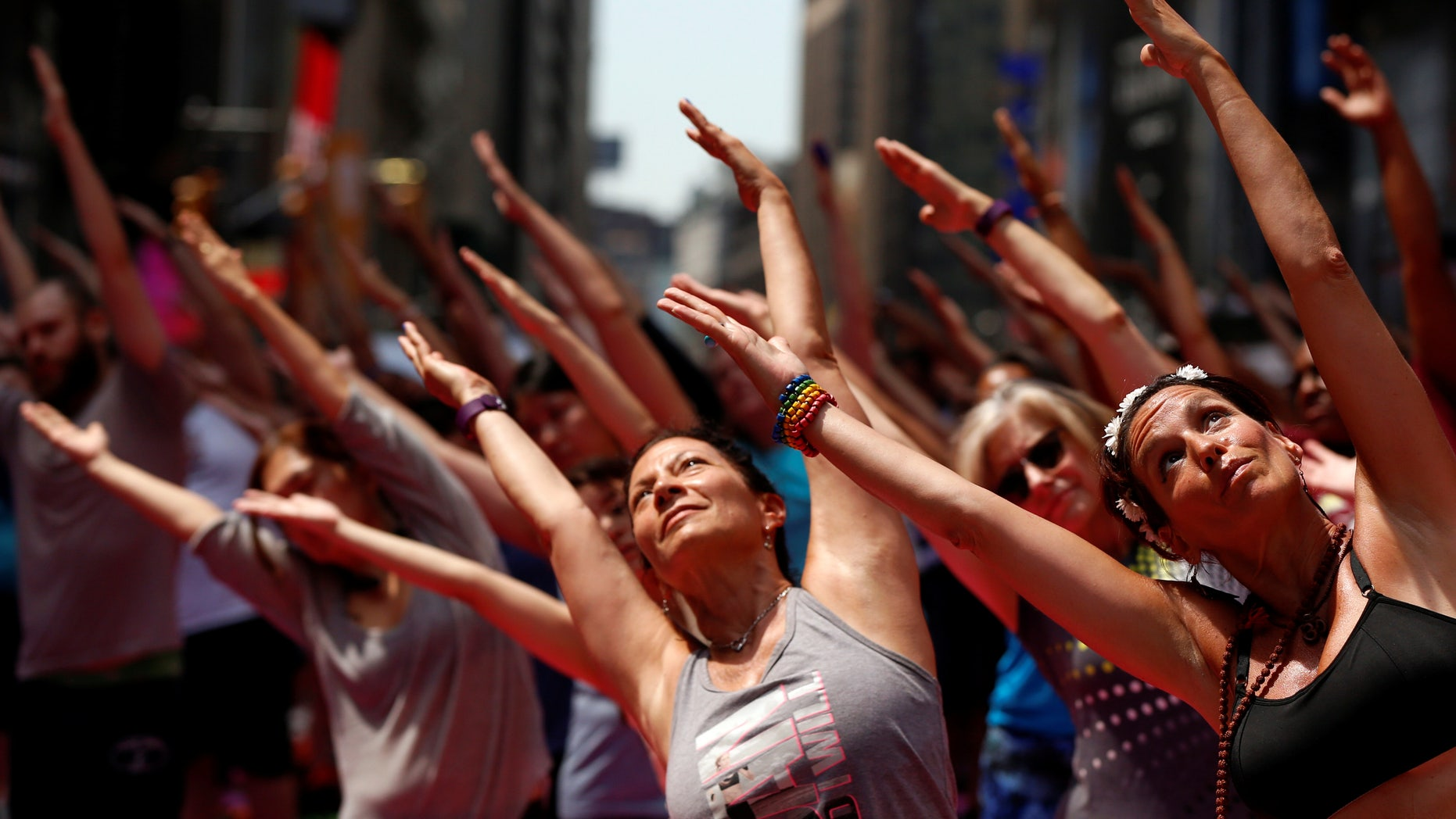 People participate in a yoga class during the 14th Annual Solstice in Times Square event in New York, U.S., June 20, 2016