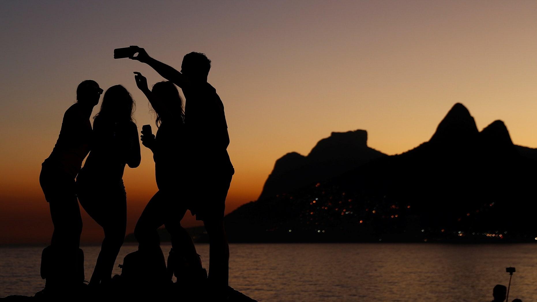 People take selfies during sunset on the rocks of Arpoador beach in Rio de Janeiro, Brazil July 4, 2016.