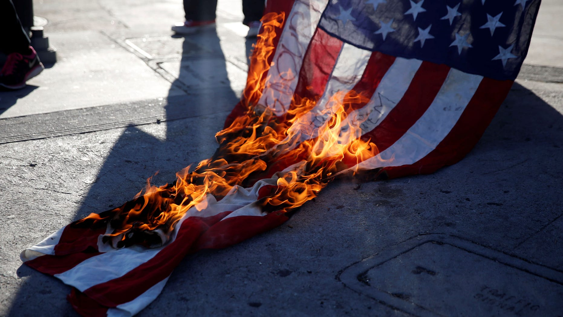Activists burn a flag while protest on the corner of Florence Ave and Normandie Ave against the police shootings that lead to two deaths in Louisiana and Minnesota, respectively, in Los Angeles, California, U.S. July 7, 2016.  REUTERS/Patrick T. Fallon - RTX2K9GY