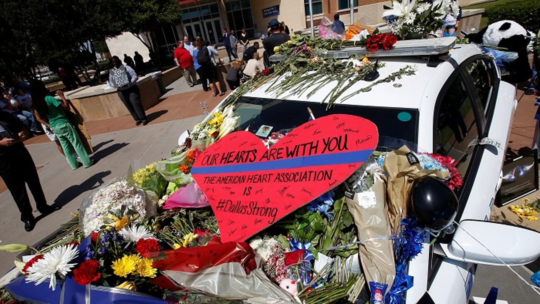 FILE -- A heart is pictured on a police car that makes up part of a makeshift memorial at Police Headquarters following the multiple police shooting in Dallas, Texas, U.S.,July 8, 2016.