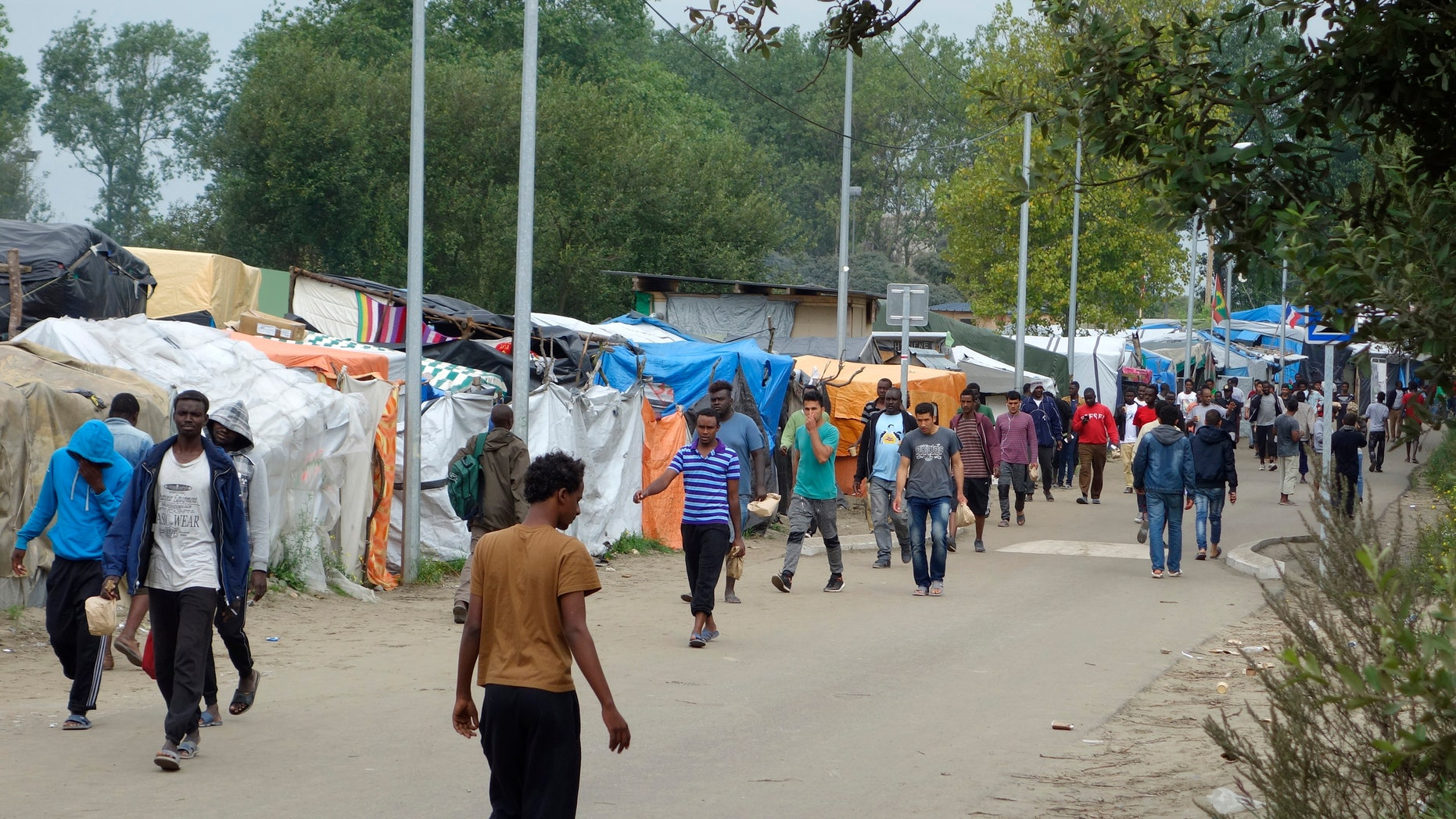"""Sept. 6, 2016: Migrants walk in the northern area of the camp called the """"Jungle"""" in Calais, France."""