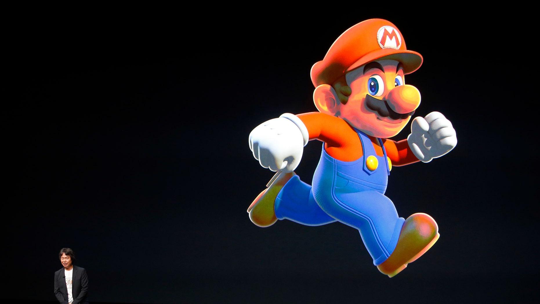 Nintendo Creative Fellow Shigeru Miyamoto stands next to the Super Mario character during an Apple media event in San Francisco, California, U.S. September 7, 2016.