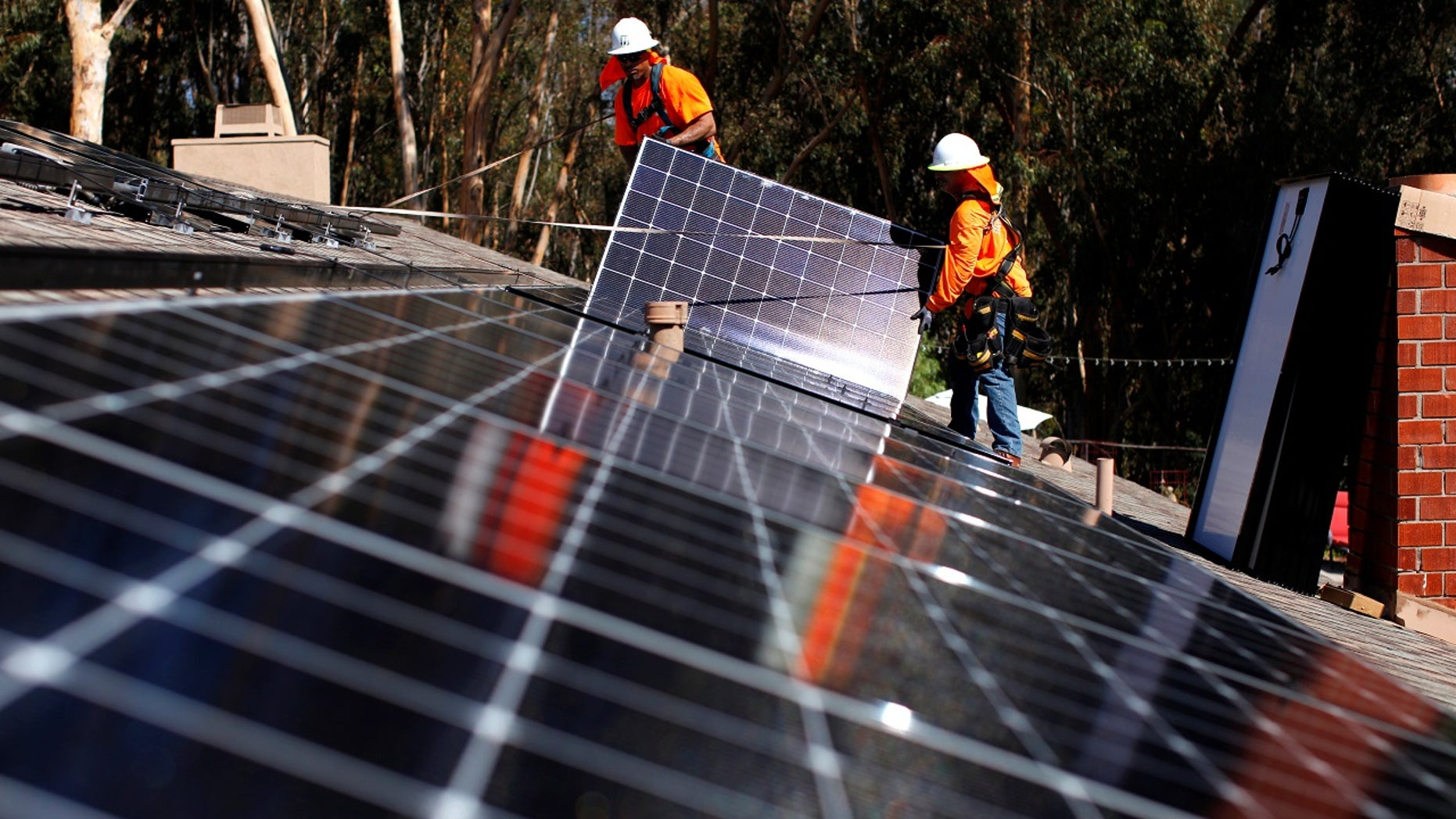 Solar installers from Baker Electric place solar panels on the roof of a residential home in Scripps Ranch, San Diego, Calif., Oct. 14, 2016.