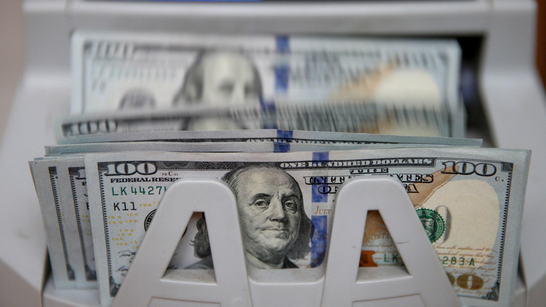 A money counter counts 100 U.S dollar banknotes in Kiev, Ukraine, October 31, 2016. (REUTERS/Valentyn Ogirenko)