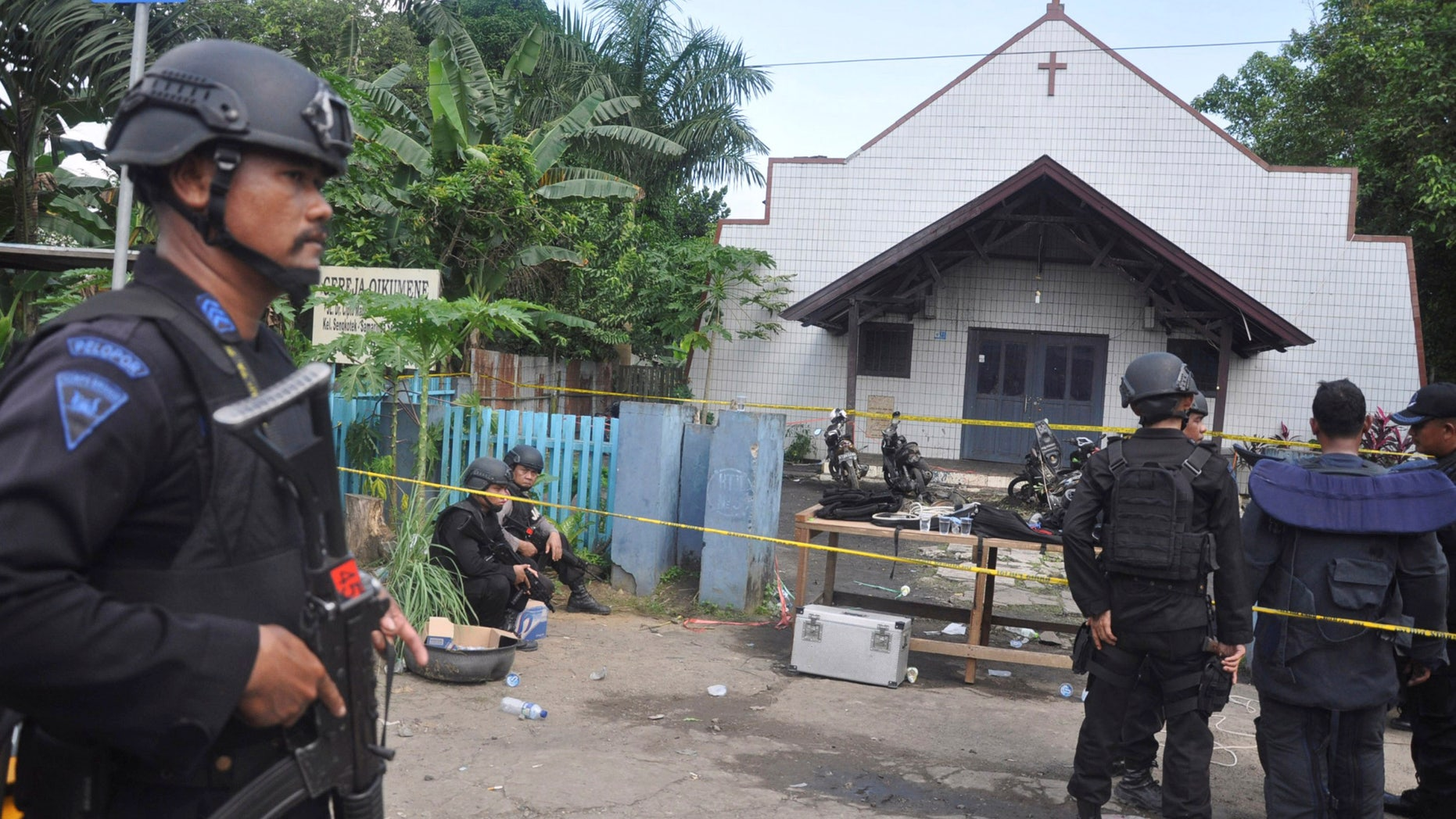 Police stand near the scene of the explosion outside a church in Samarinda.
