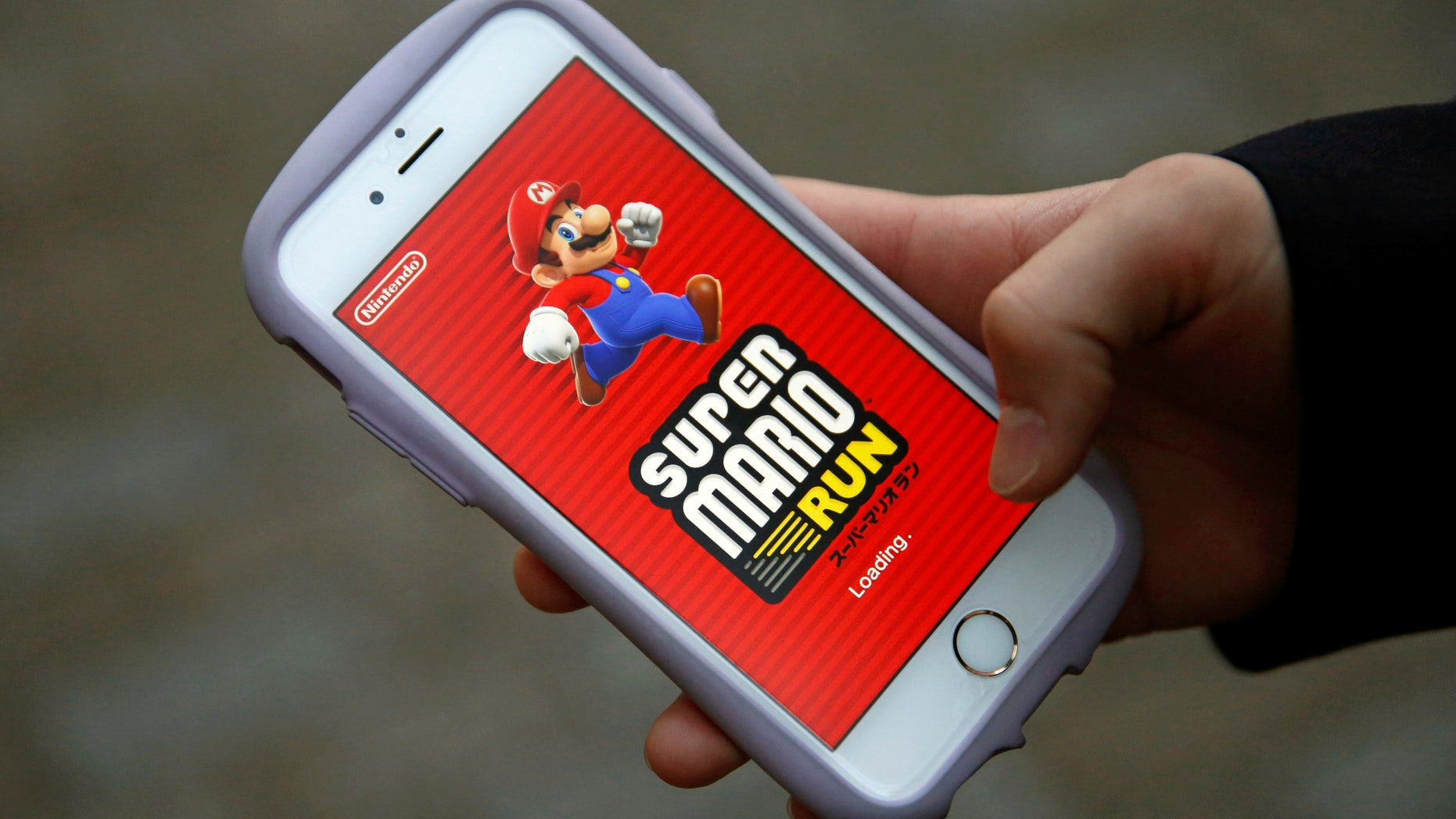 "Takuya Nishya shows Nintendo's ""Super Mario Run"" game on his smartphone by the request of a photographer in Tokyo, Japan, December 20, 2016. (REUTERS/Kim Kyung-Hoon)"