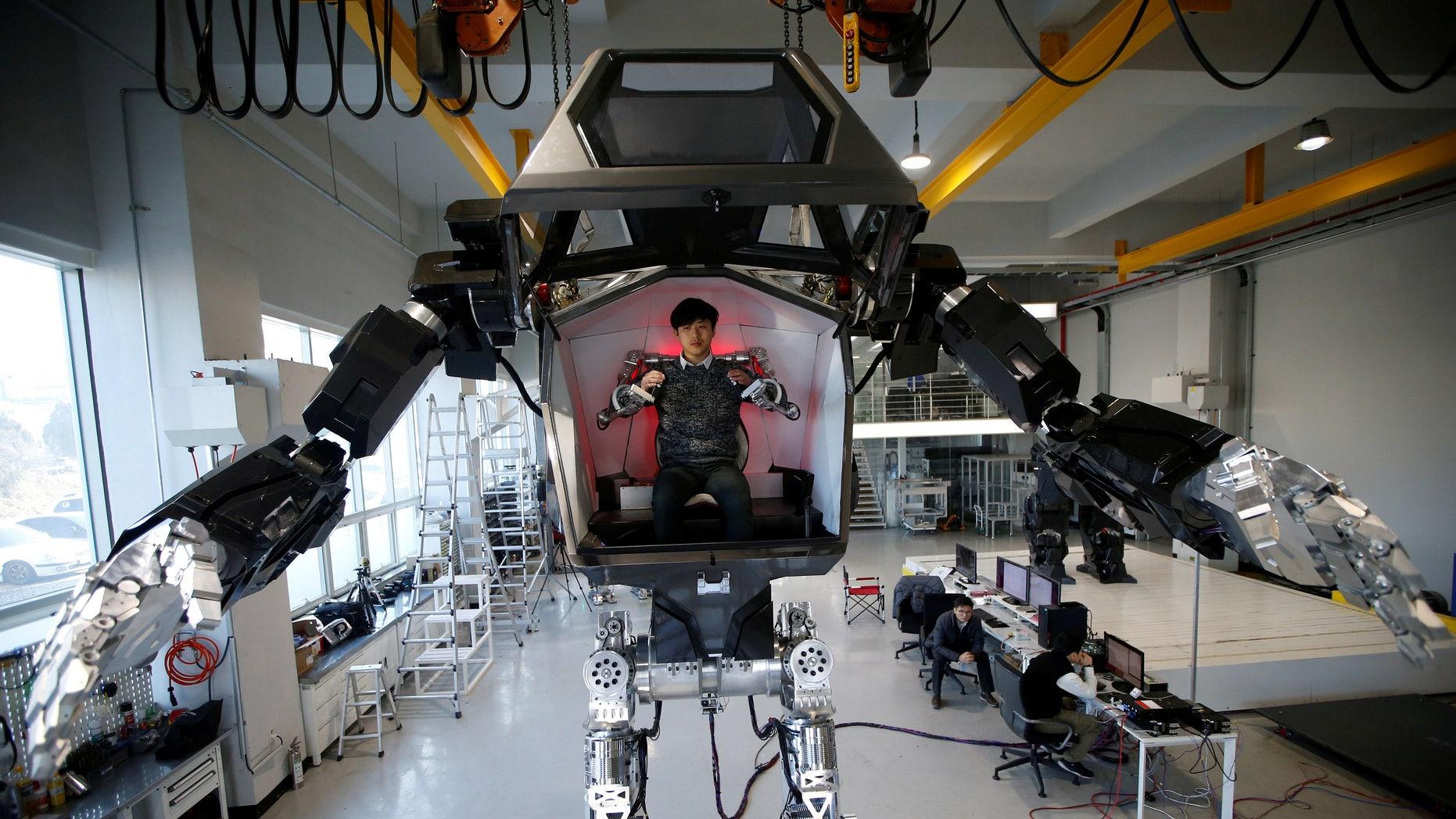 "An employee controls the arms of a manned biped walking robot ""METHOD-2"" during a demonstration in Gunpo, South Korea, December 27, 2016. (REUTERS/Kim Hong-Ji)"