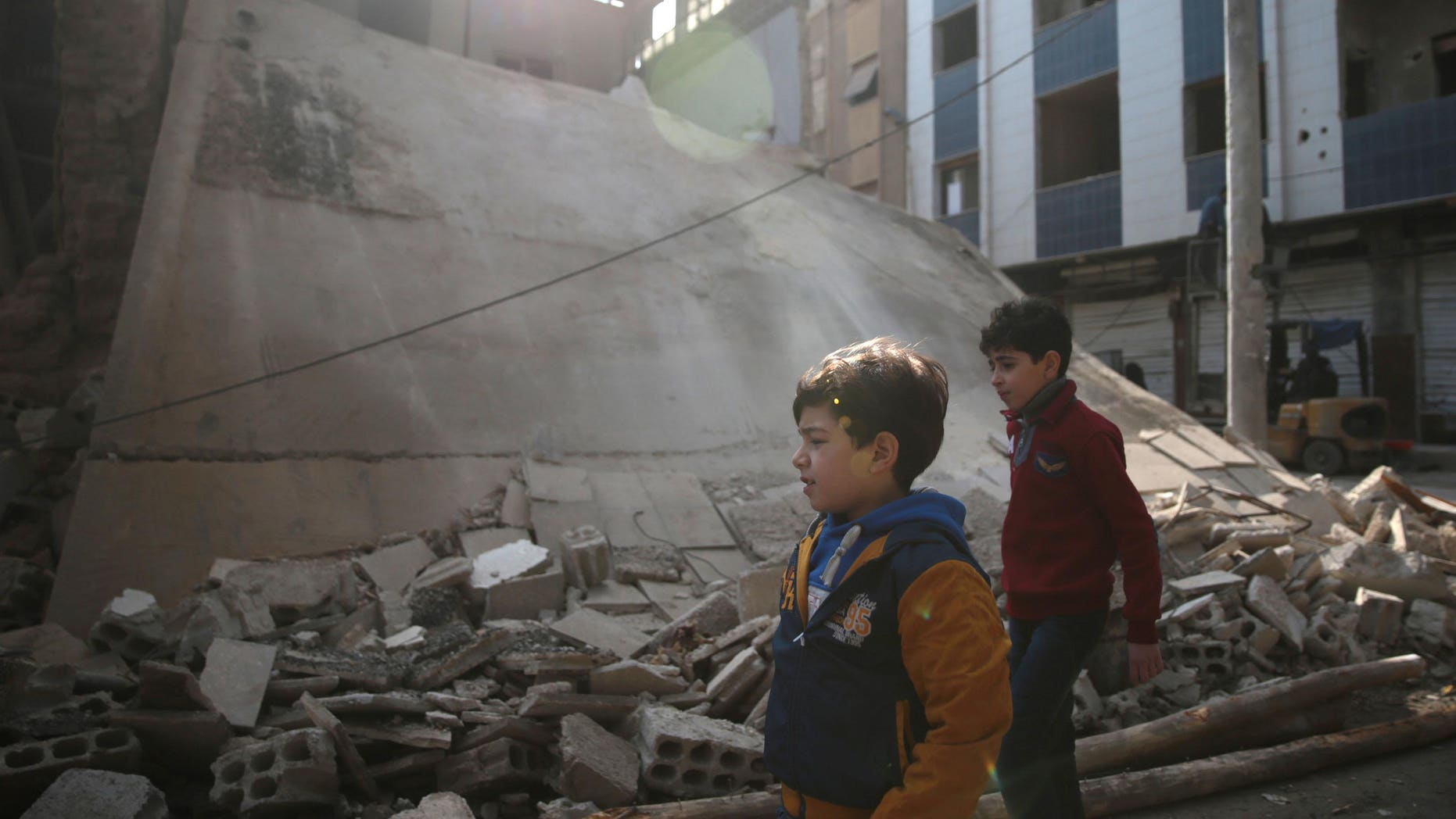 Boys walk near a damaged building in the rebel held besieged city of Douma, in the eastern Damascus suburb of Ghouta, Syria December 30, 2016. REUTERS/Bassam Khabieh - RTX2WYAO