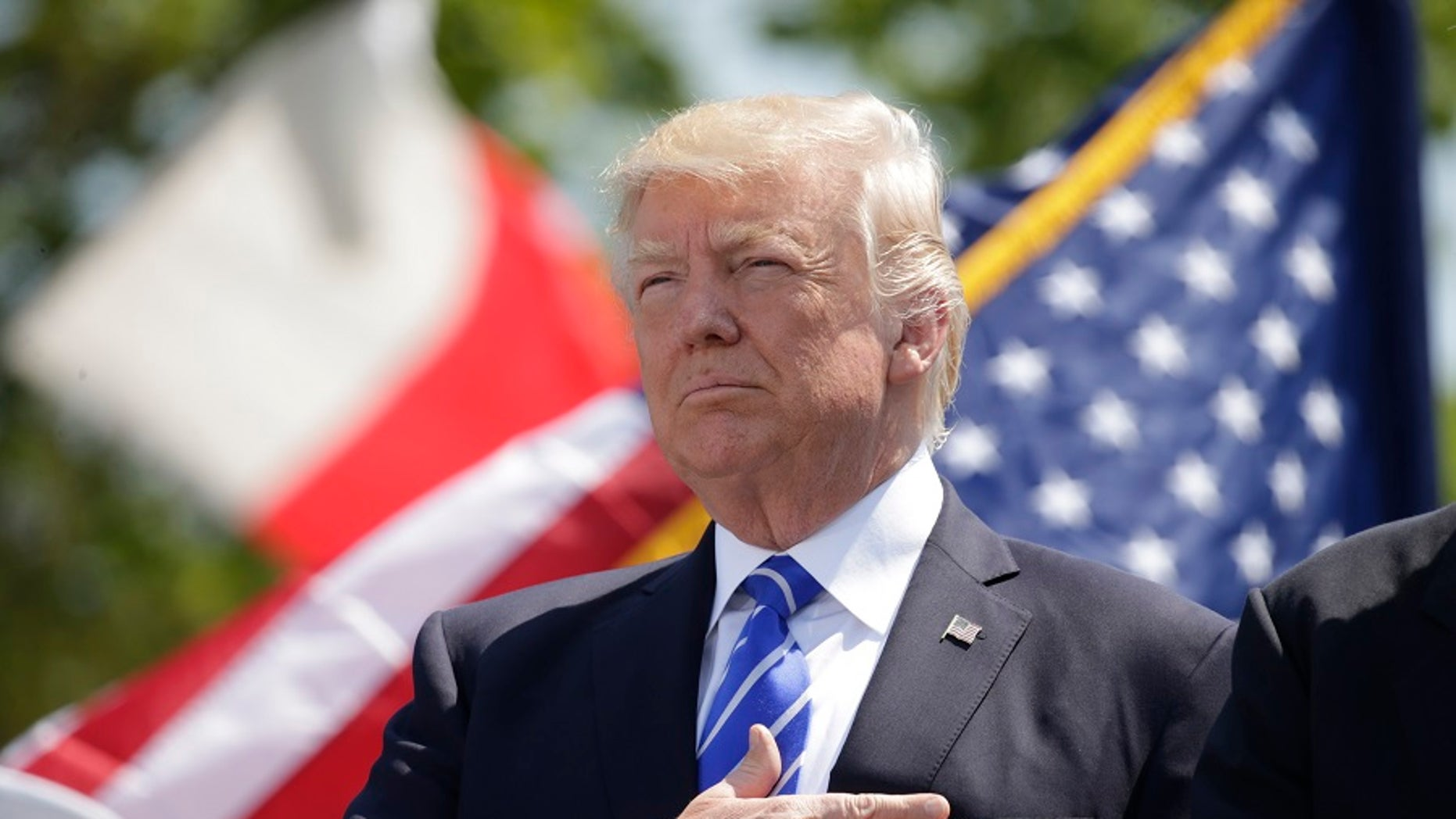 President Donald Trump holds his hand over his heart for the U.S. National Anthem as he attends the Coast Guard Academy commencement ceremonies to address the graduating class in New London, Connecticut, U.S. May 17, 2017.