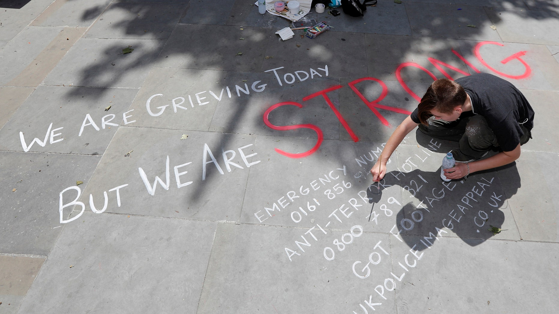 A man writes a message on the pavement in central Manchester, Britain May 23, 2017.