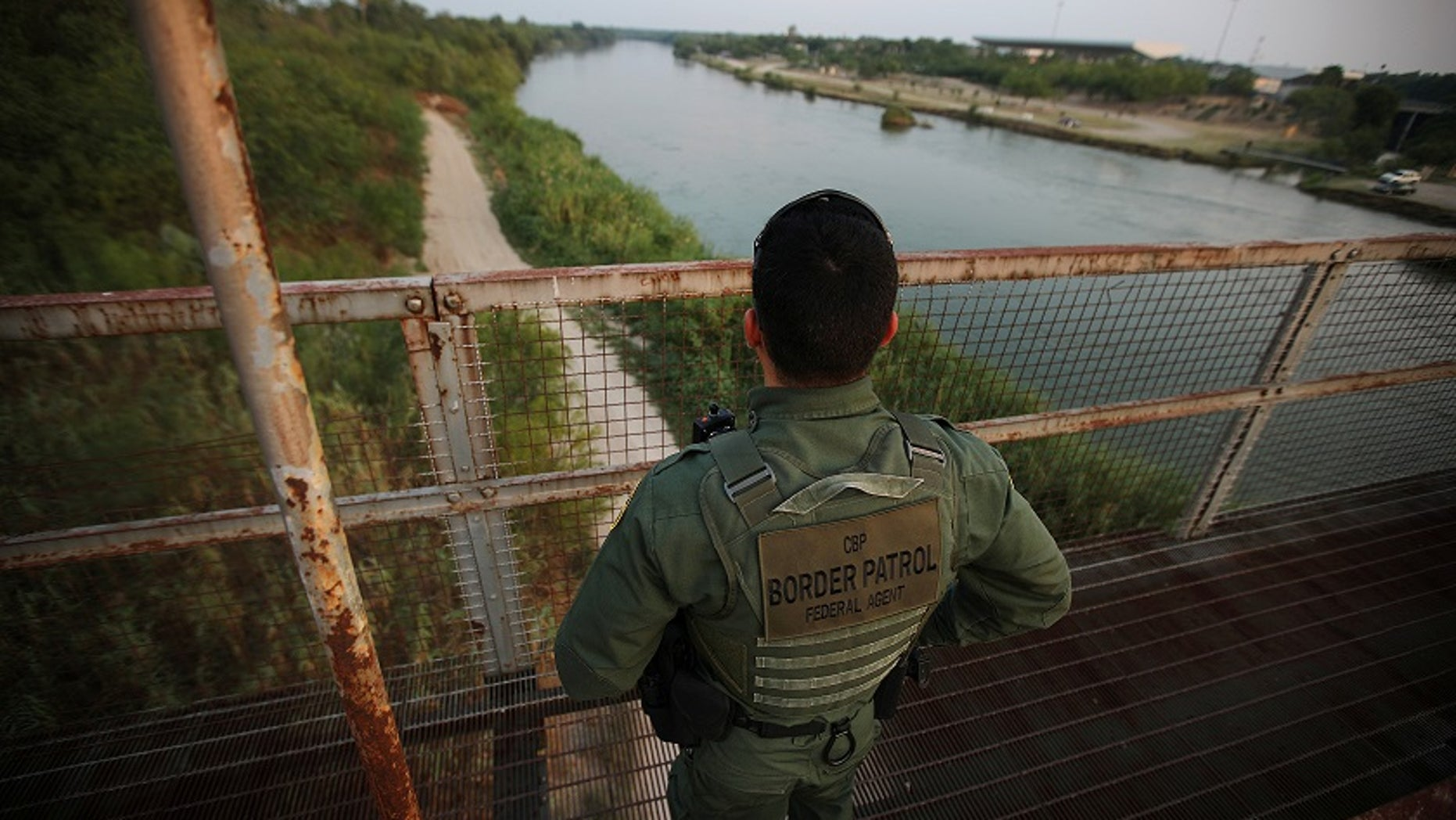 A U.S. Border Patrol agent looks over the Rio Grande River at the border between the U.S. and Mexico in Roma, Texas.